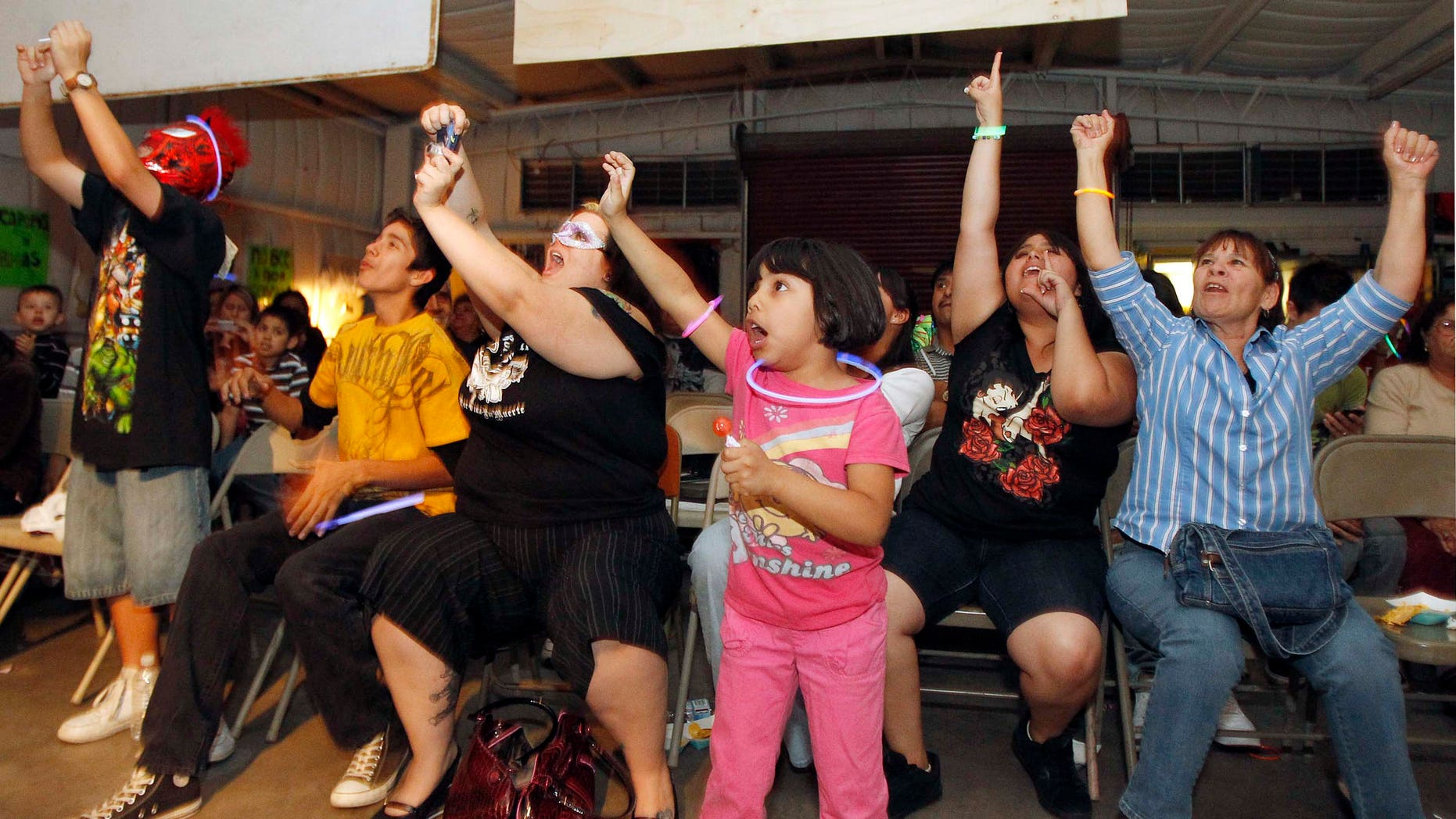 This Friday, April 30, 2010 photo shows fans as they cheer during a match at a Lucha Libre Mexican wrestling night, part of Lucha Libre Internacional Gladiadores Unidos, at a family friendly venue in Phoenix. (AP Photo/Ross D. Franklin)