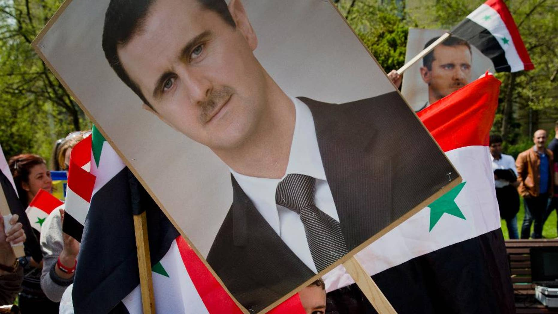 A child of the Syrian community in Romania peers from behind a picture of Syrian President Bashar Assad, during a rally in Bucharest, Romania, Sunday, April 9, 2016. Syrians gathered in a protest against foreign support for the rebel groups in Syria and voiced their support for the country's president Bashar Assad and his regime. (AP Photo/Vadim Ghirda)
