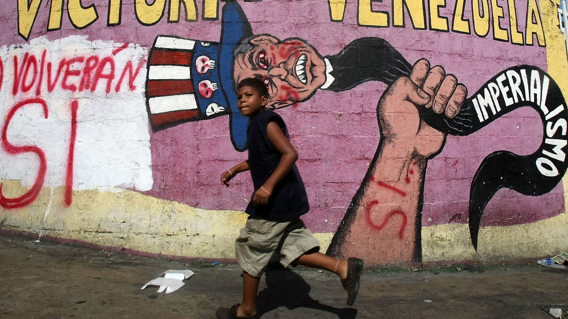 """CARACAS, VENEZUELA - DECEMBER 01:  A boy runs past anti-American propaganda and graffiti reading """"Si"""" signifying support for a referendum on changes to the Constitution introduced by Venezuelan President Hugo Chavez December 1, 2007 in Caracas, Venezuela.  Sunday's referendum proposes an elimination of term limits for Chavez and a transformation of Venezuela into a """"socialist economy.""""  (Photo by Mario Tama/Getty Images)"""
