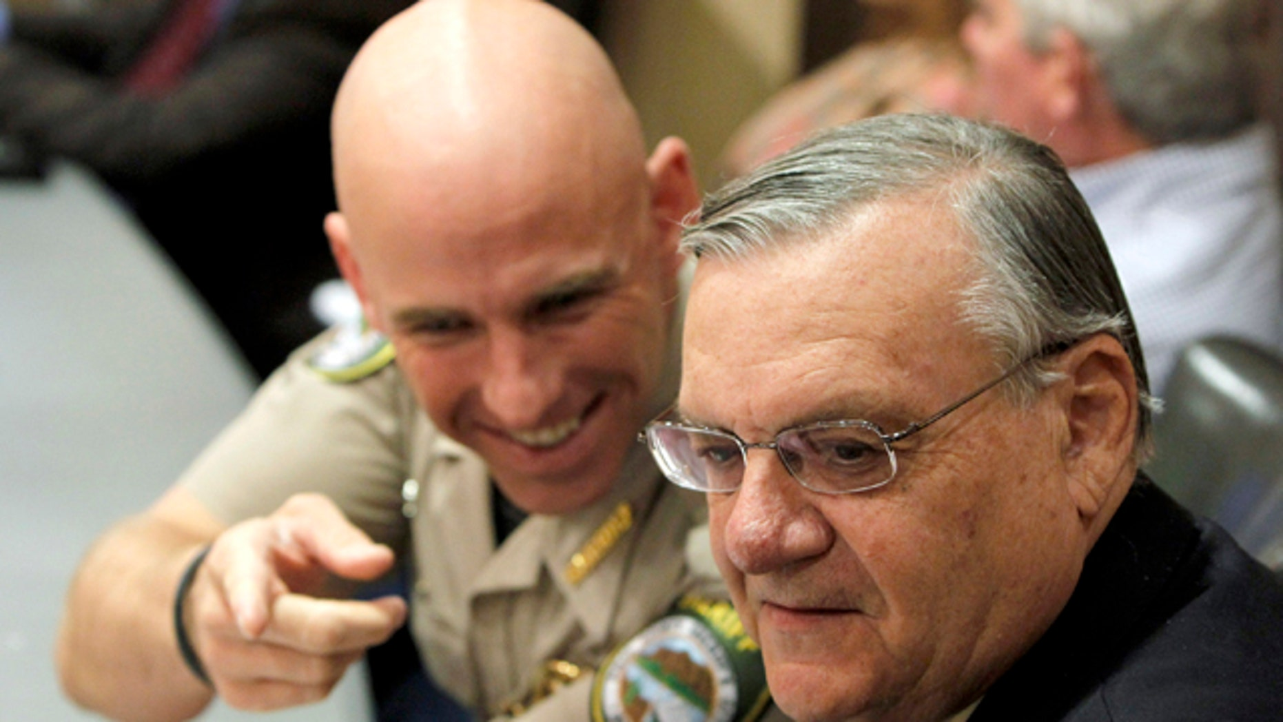 Pinal County Sheriff Paul Babeu, left, talks with Maricopa County Sheriff Joe Arpaio during a meeting last year. In response to a letter from three local mayors asking him to tone down his rhetoric, Babeu said his jurisdiction is the 'number one pass through county' nationwide for smuggling people and drugs. (AP)