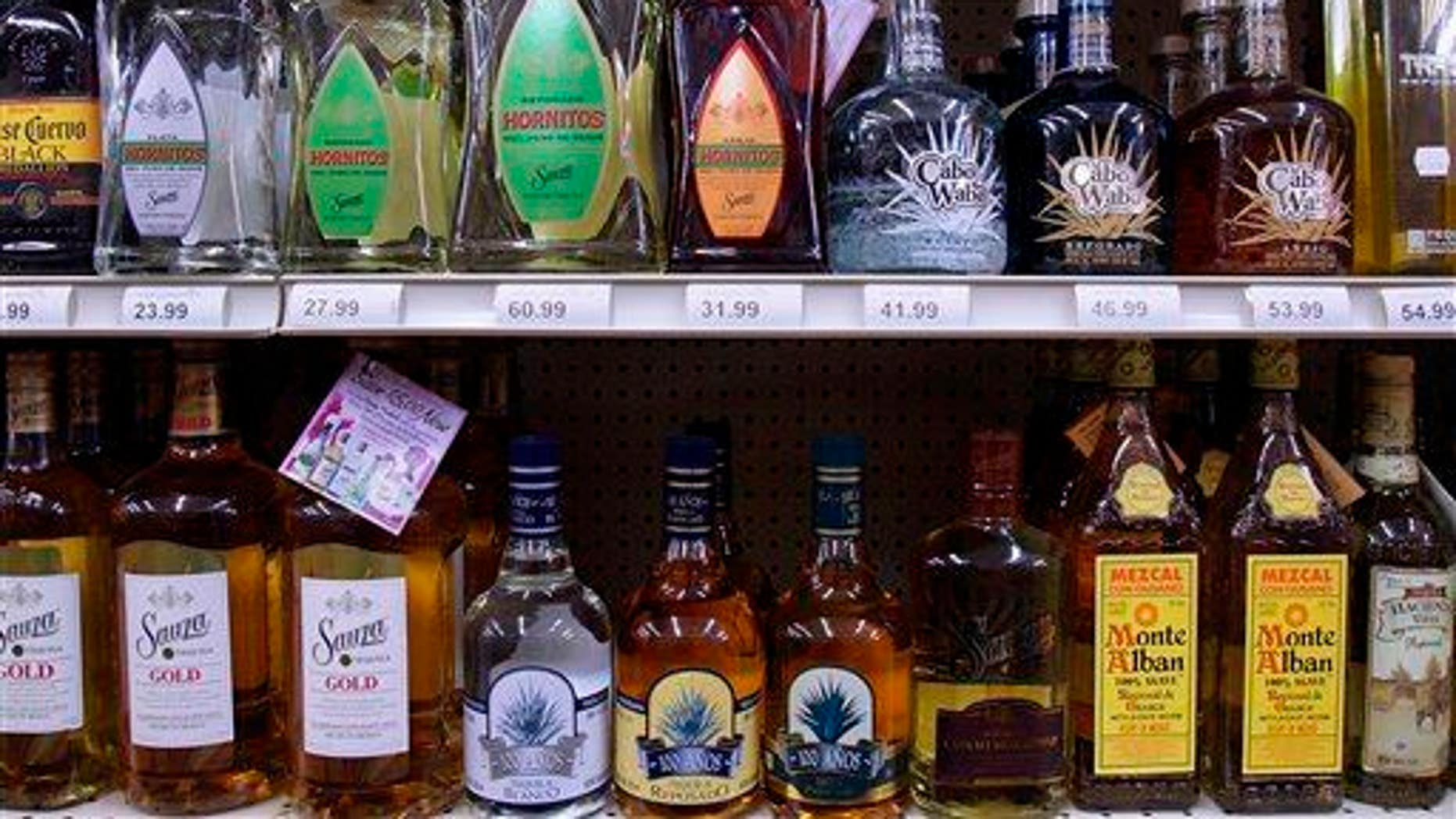 In this Monday, Aug. 31, 2009 file photo, bottles of alcohol are seen lining the shelves of a liquor store in Springfield, Ill. It's the time of year that social host liability laws can leave parents vulnerable for teens drinking under their roofs.