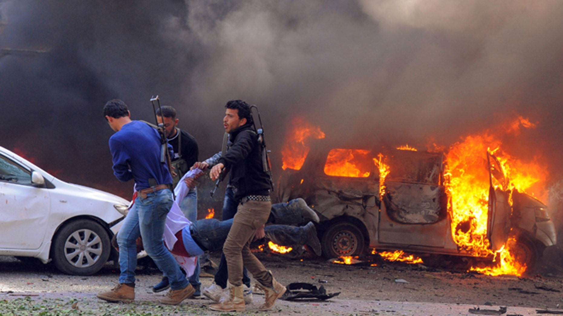 Feb. 21, 2013: In this photo provided by the Syrian official news agency SANA, Syrian security agents carry a body following a huge explosion that shook central Damascus, Syria.