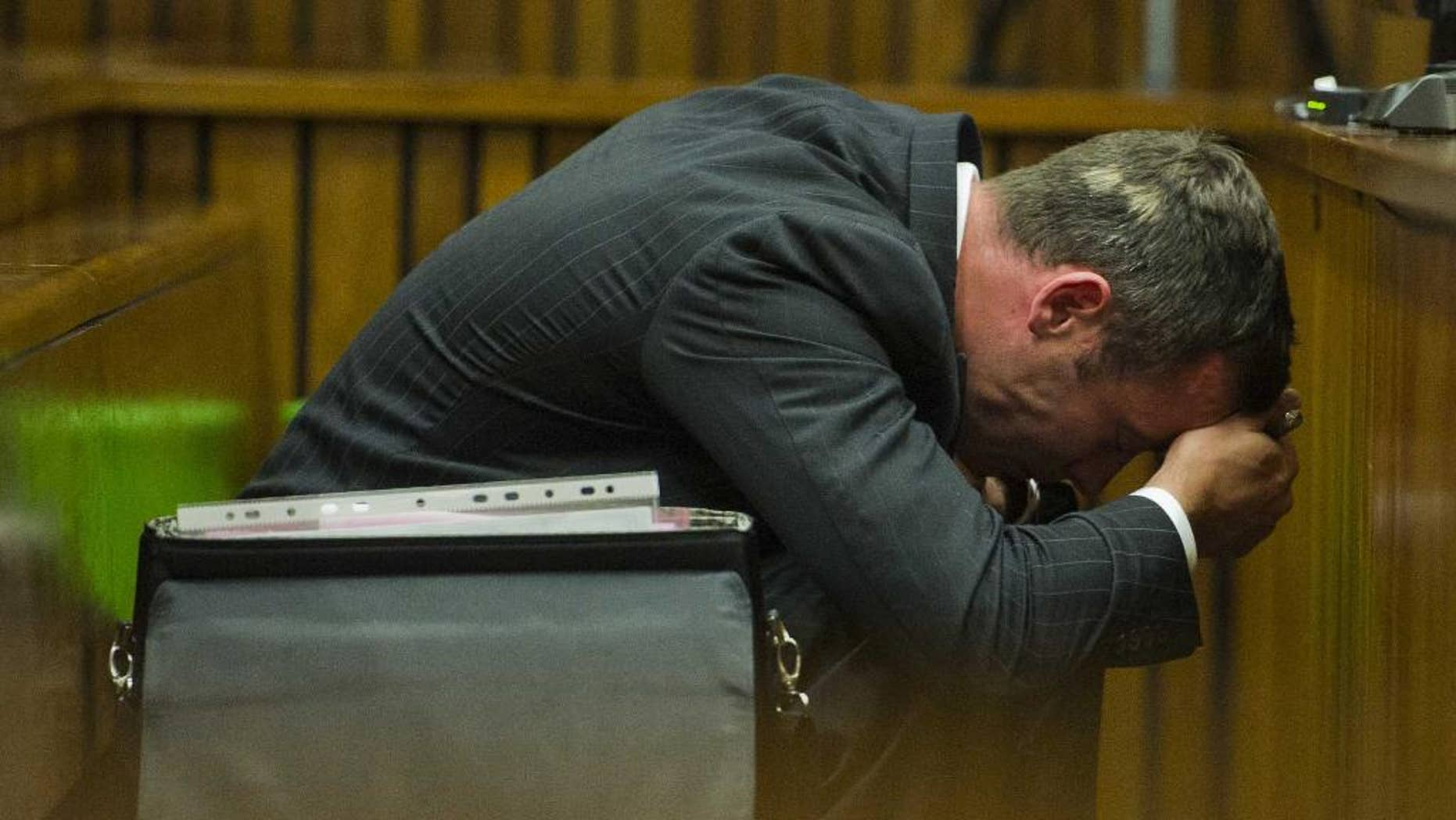 Oscar Pistorius puts his hands to his head as he listens to forensic evidence during his trial in court in Pretoria, South Africa, Thursday March 13, 2014. Pistorius is charged with the shooting death of his girlfriend Reeva Steenkamp on Valentines Day in 2013. (AP Photo/Alet Pretorius, Pool)