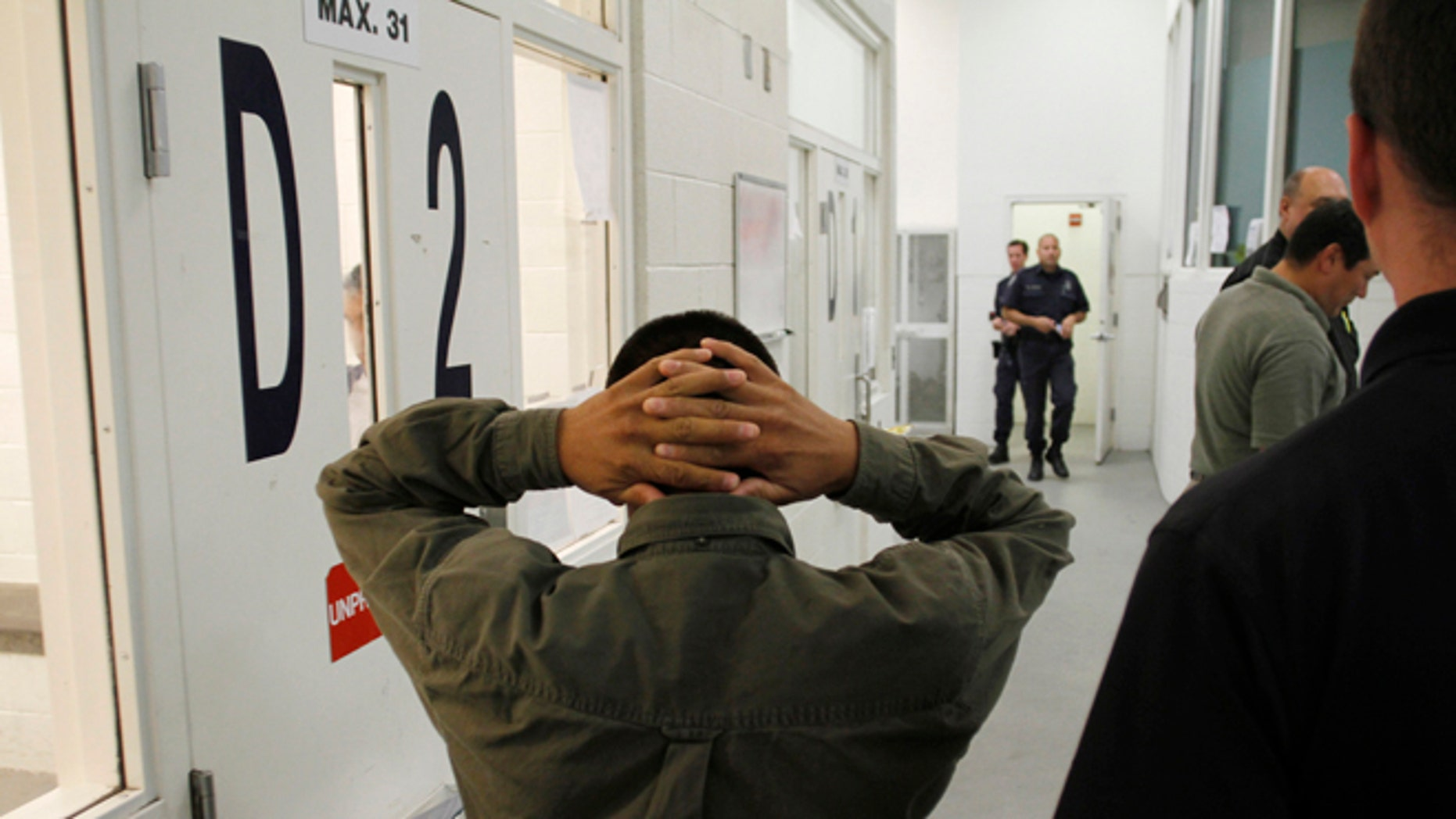 An undocumented immigrant is escorted at the Immigration and Customs Enforcement holding facility.