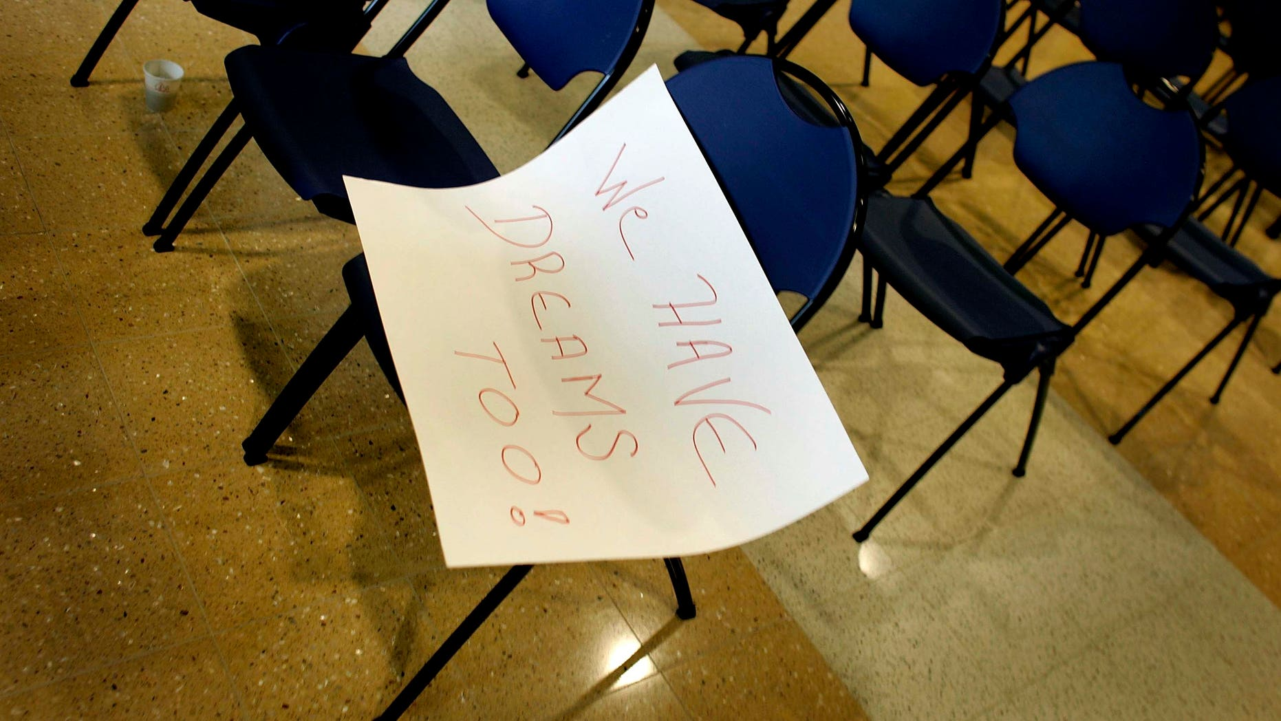 "MIAMI - MARCH 12:  A sign with the words, "" We have dreams too!"", lays on a chair after a press conference to announce The American Dream Act March 12, 2007 at Florida International University in Miami, Florida. The bill, if passed in the United States Congress, would allow for undocumented immigrant students to obtain in-state tuition as well as permit those students, along with those serving in the military, to obtain a green card and legally remain in the United States.  (Photo by Joe Raedle/Getty Images)"