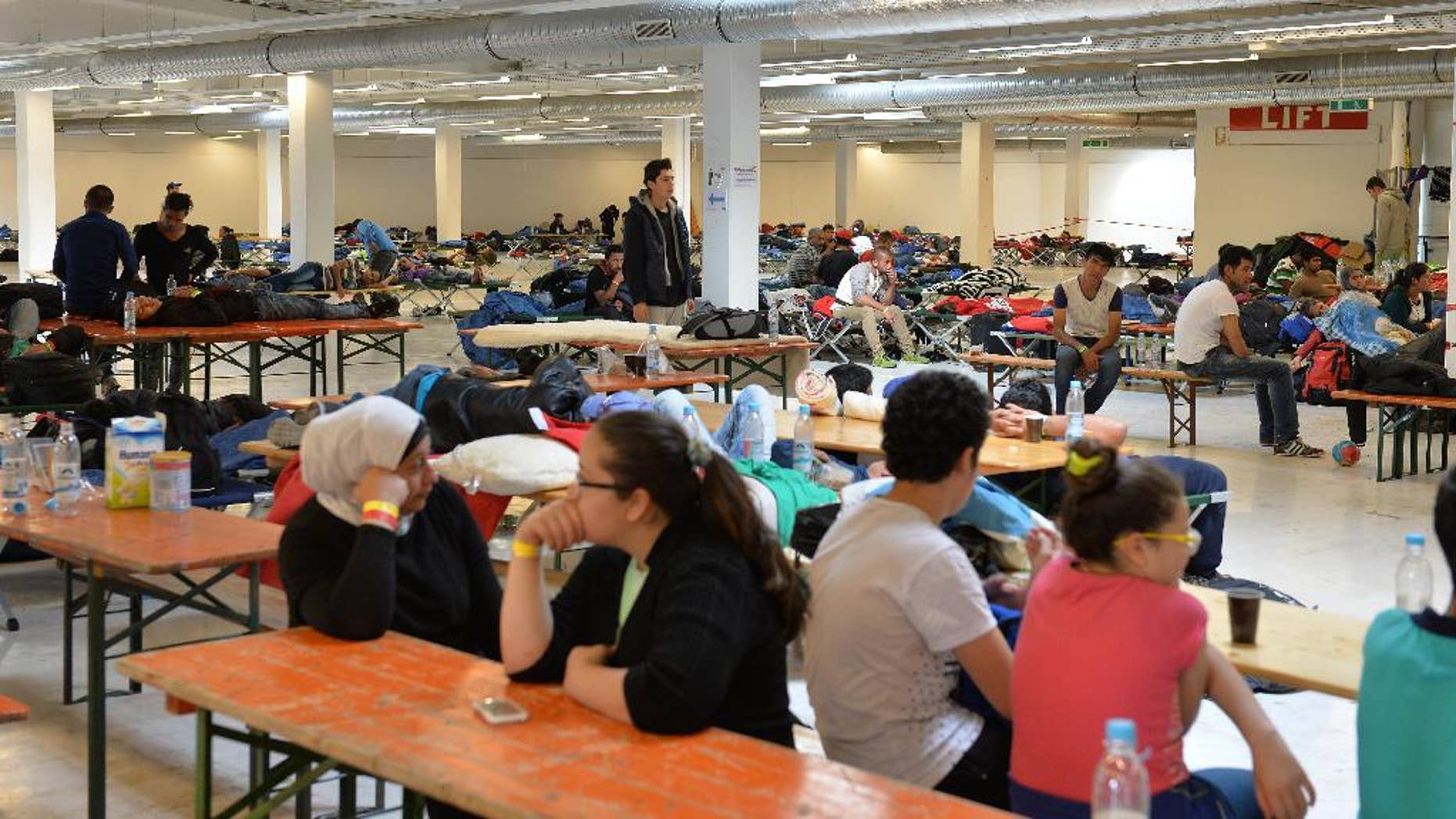 Refugees rest in a former furniture factory after crossing the border from Austria in Freilassing, southern Germany, Thursday, Sept. 17, 2015. (AP Photo/Kerstin Joensson)