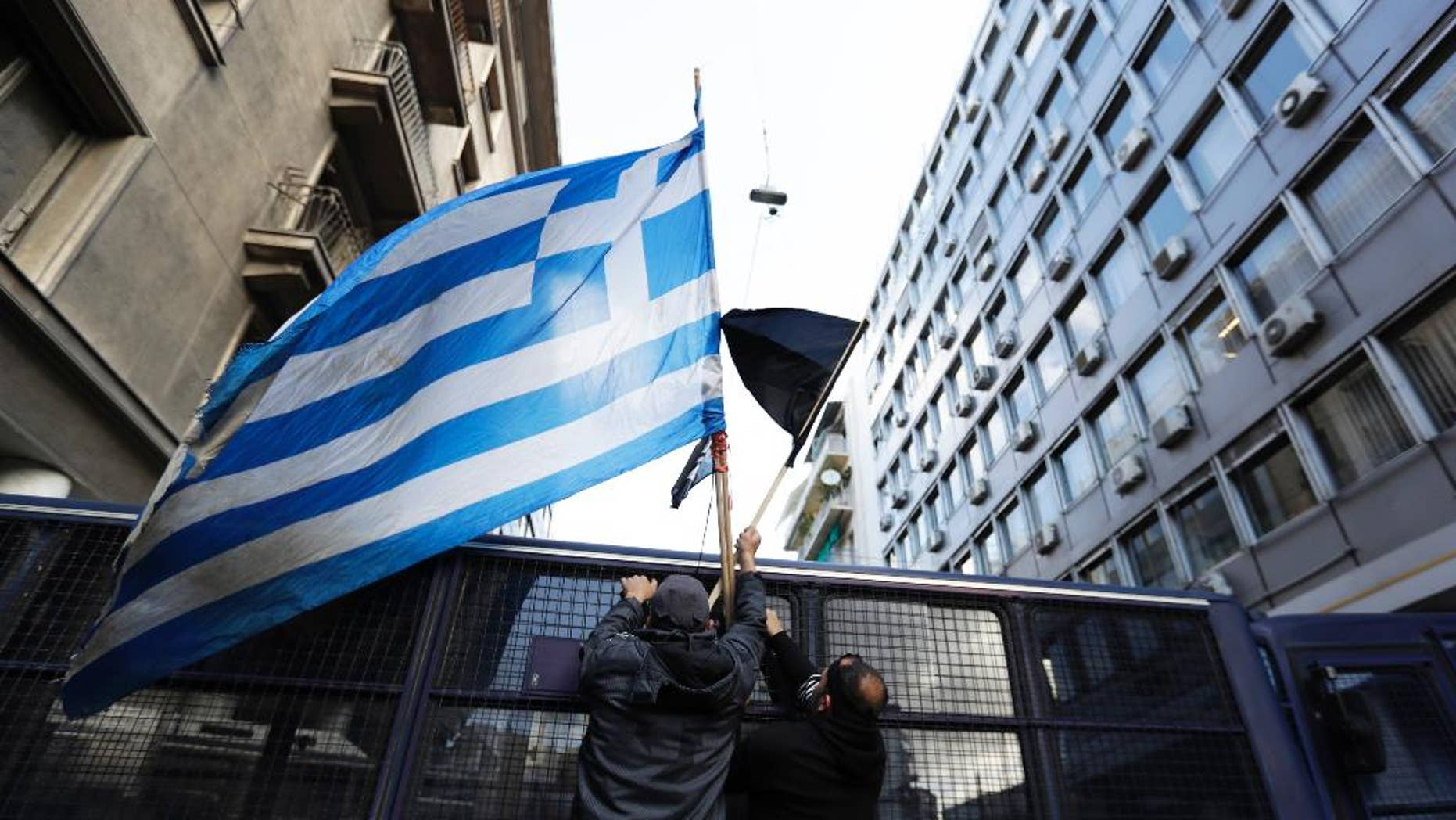 Protesting farmers place a greek flag on a police vehicle outside the Greek Agriculture Ministry, in Athens, Wednesday, March 8, 2017. Several hundred farmers from the island of Crete are protesting against government tax reforms tied to the country's international bailout. (AP Photo/Thanassis Stavrakis)