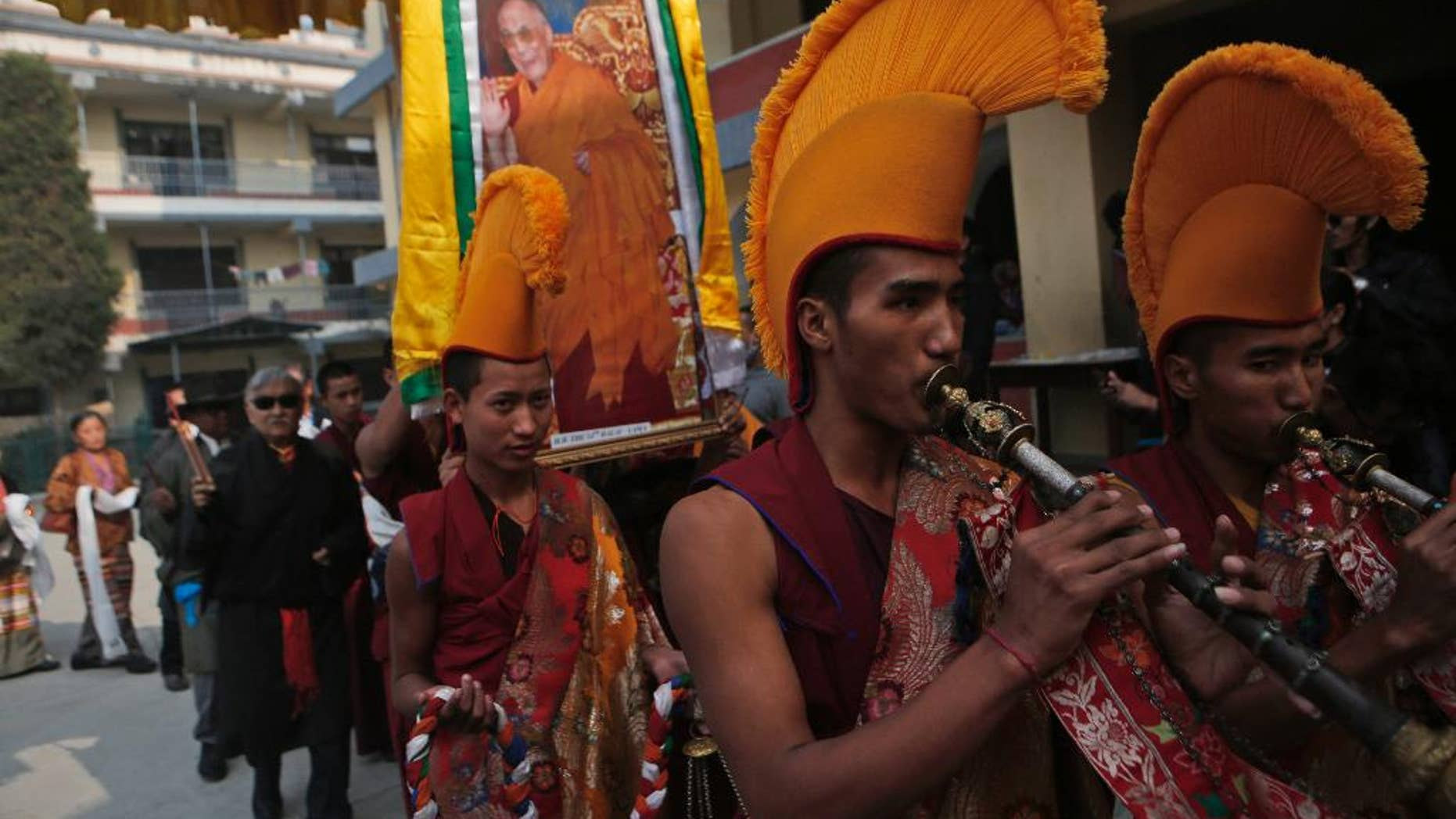 Tibetan monks carry a portrait of their spiritual leader the Dalai Lama and play traditional instruments during a special prayer ceremony on the third day of the Tibetan New Year celebrations in Kathmandu, Nepal, Wednesday, March 1, 2017. (AP Photo/Niranjan Shrestha)