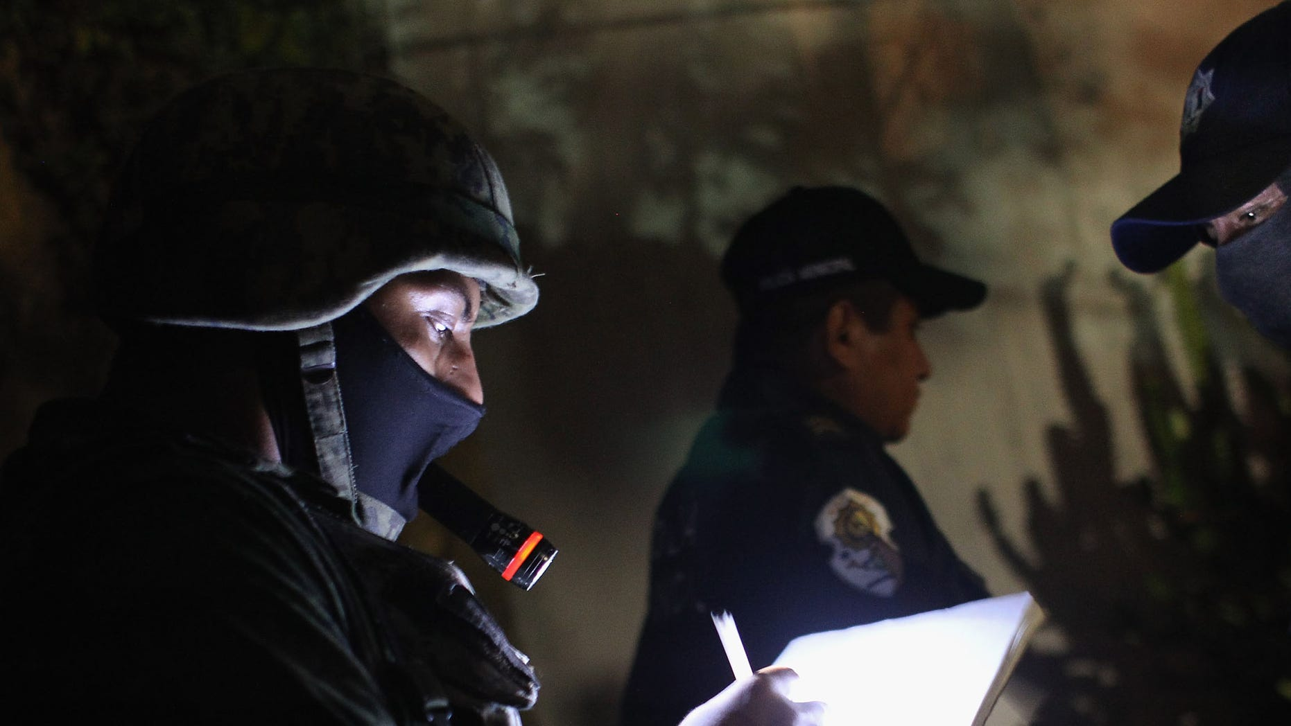 A Mexican soldier takes notes at a suspected drug-related murder site late.