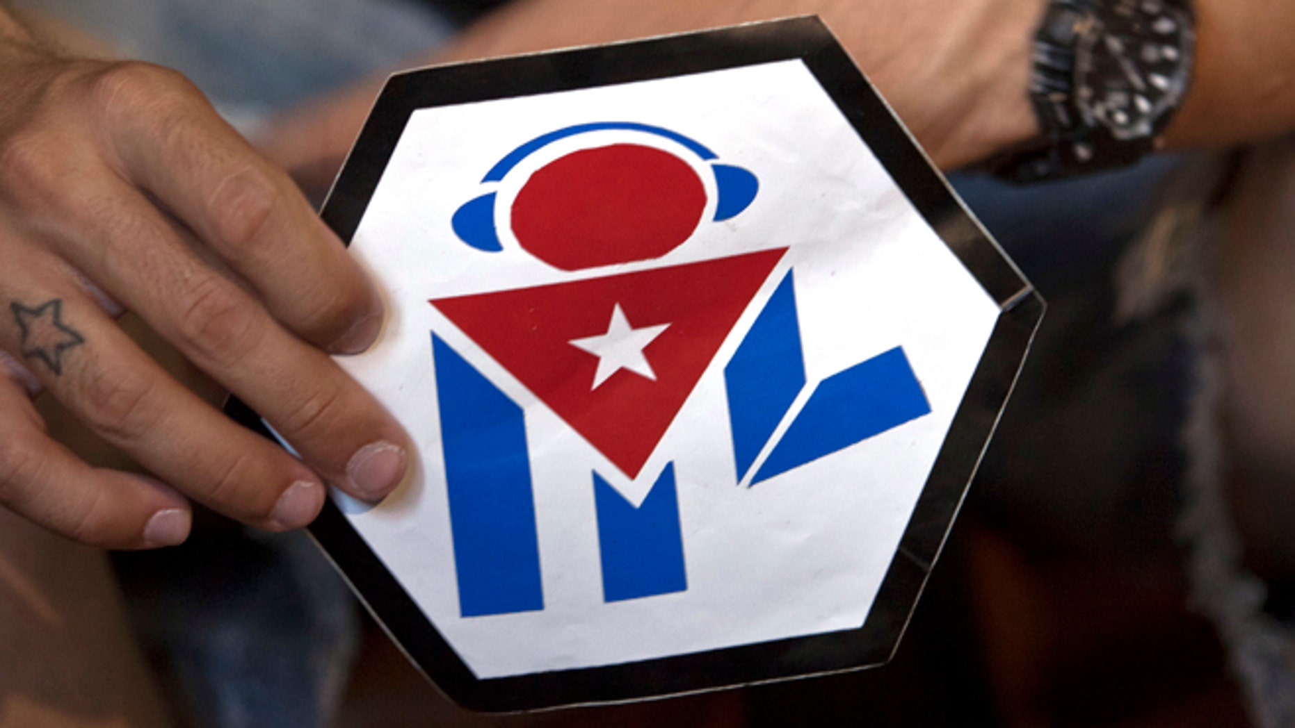 """In this July 11, 2014, photo, Manuel Barbosa, 25, shows the logo of his """"Revolution"""" audiovisual project during an interview with The Associated Press in Santa Clara, Cuba. Fernando Murillo contacted Barbosa, a founder of the group, while working on a clandestine operation by the Obama administration that dispatched Latin American youth to Cuba under the cover of health and civic programs to provoke unrest. Barbosa said he was initially open to collaboration with the foreigners but was never told they were working for the U.S. """"They presented themselves as a non-governmental organization,"""" Barbosa said. (AP Photo/Franklin Reyes)"""