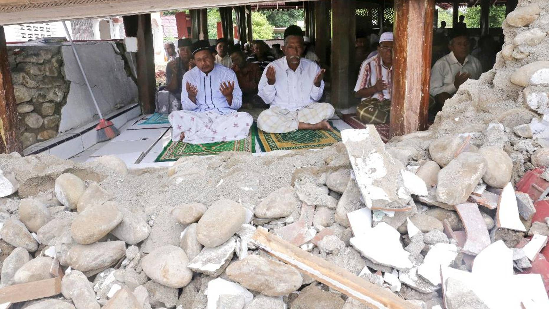 Survivors perform Friday prayer at a mosque badly damaged by Wednesday's earthquake in Pidie, Aceh province, Indonesia, Friday, Dec. 9, 2016. Over one hundred people were killed in the quake that hit the northeast of the province on Sumatra before dawn Wednesday. Hundreds of people were injured and thousands buildings destroyed or heavily damaged. (AP Photo/Heri Juanda)