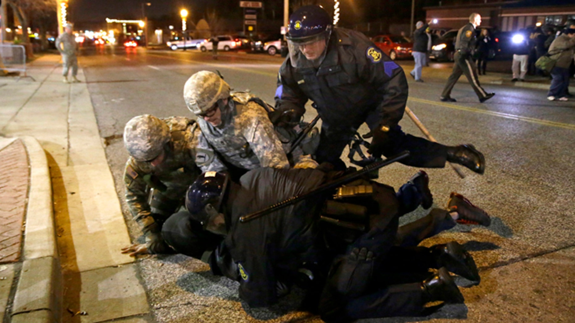 A protester is taken into custody Friday, Nov. 28, 2014, in Ferguson, Mo. Several protesters have been taken into custody during a demonstration outside the police department. Tensions escalated late Friday during an initially calm demonstration after police said protesters were illegally blocking West Florissant Avenue. (AP Photo/Jeff Roberson)