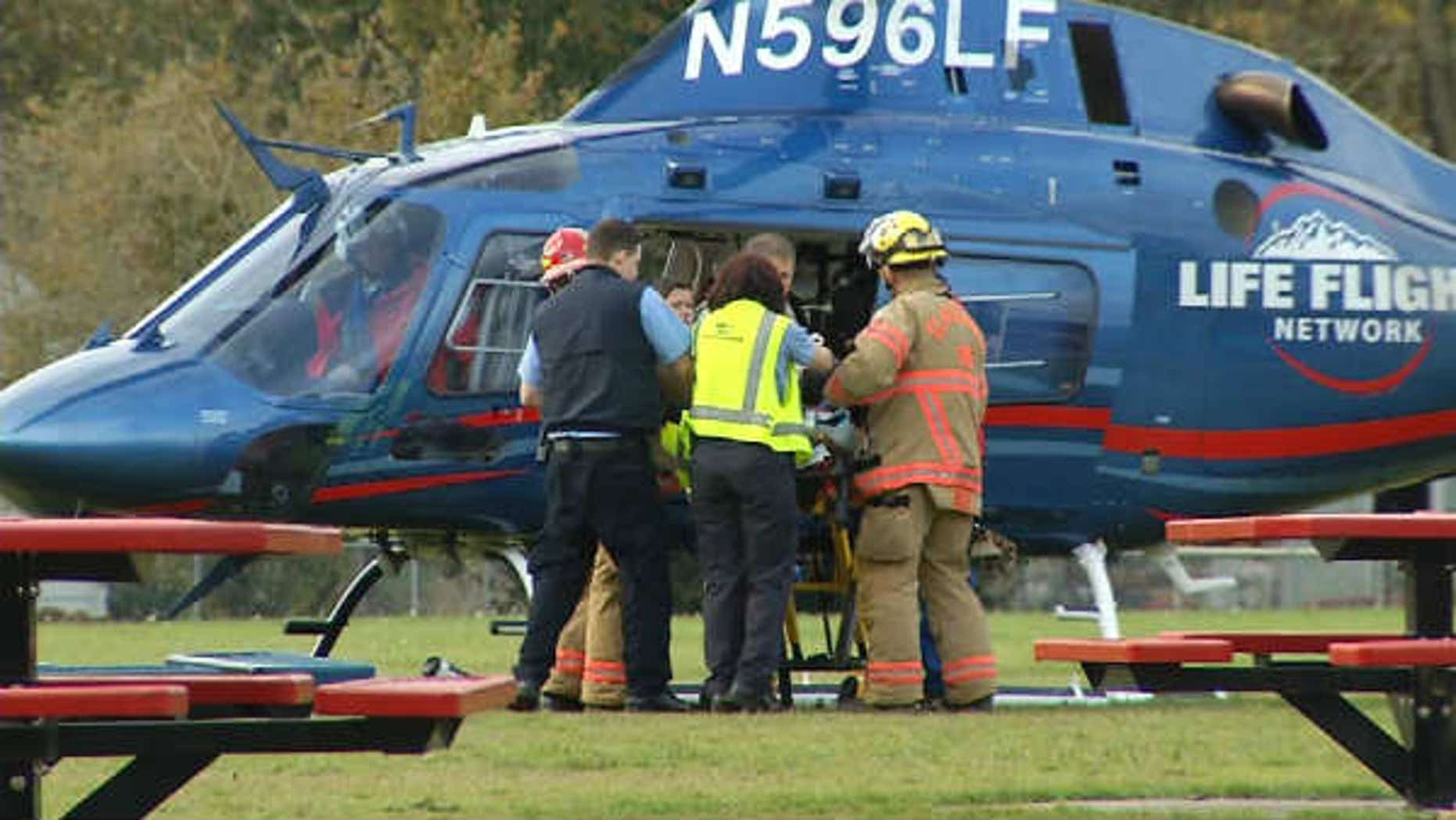 November 3, 2013: A police officer is loaded onto a helicopter after being shot responding to a fire in Oregon City, Ore. (Courtesy KPTV)
