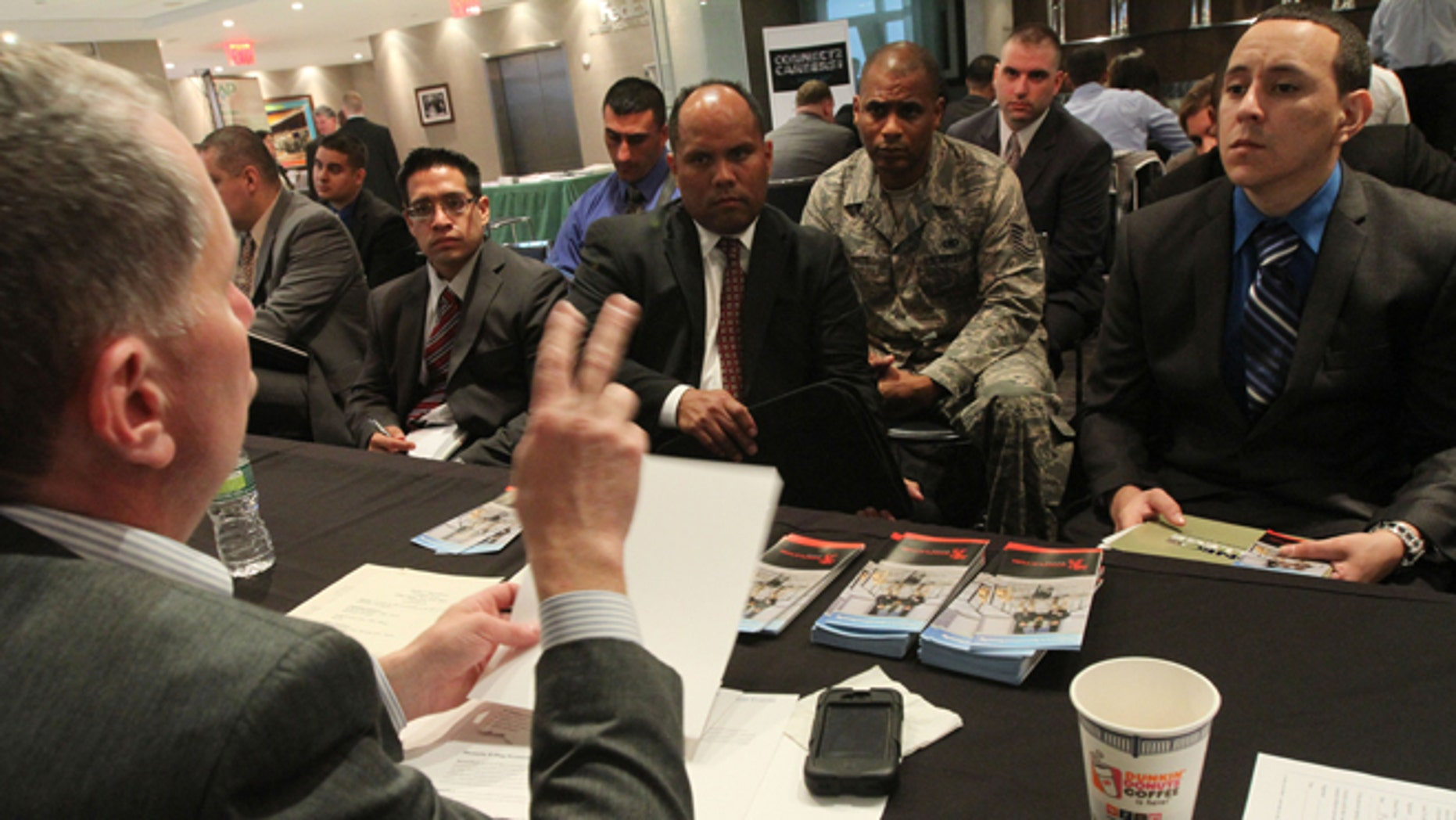 Sept. 28, 2012: Karl Hagstrom, left, of the Stapleton Group talks to veterans about his agency during a job fair introducing veterans to careers in the security and private investigations industry at Yankee Stadium in the Bronx borough of New York.