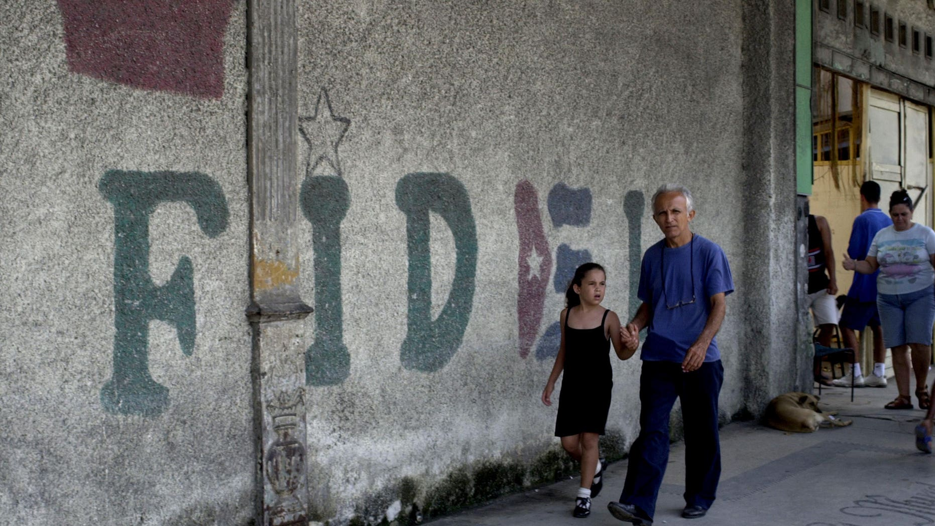 """HAVANA, CUBA - AUGUST 12:  A man walks in front of a wall that says """"Fidel"""" August 12, 2003 in Old Havana, Cuba. Cuban President Fidel Castro turns 77 August 13, 2003 and has been in power for 44 years, making him the world's longest serving head of state. (Photo by Jorge Rey/Getty Images)"""