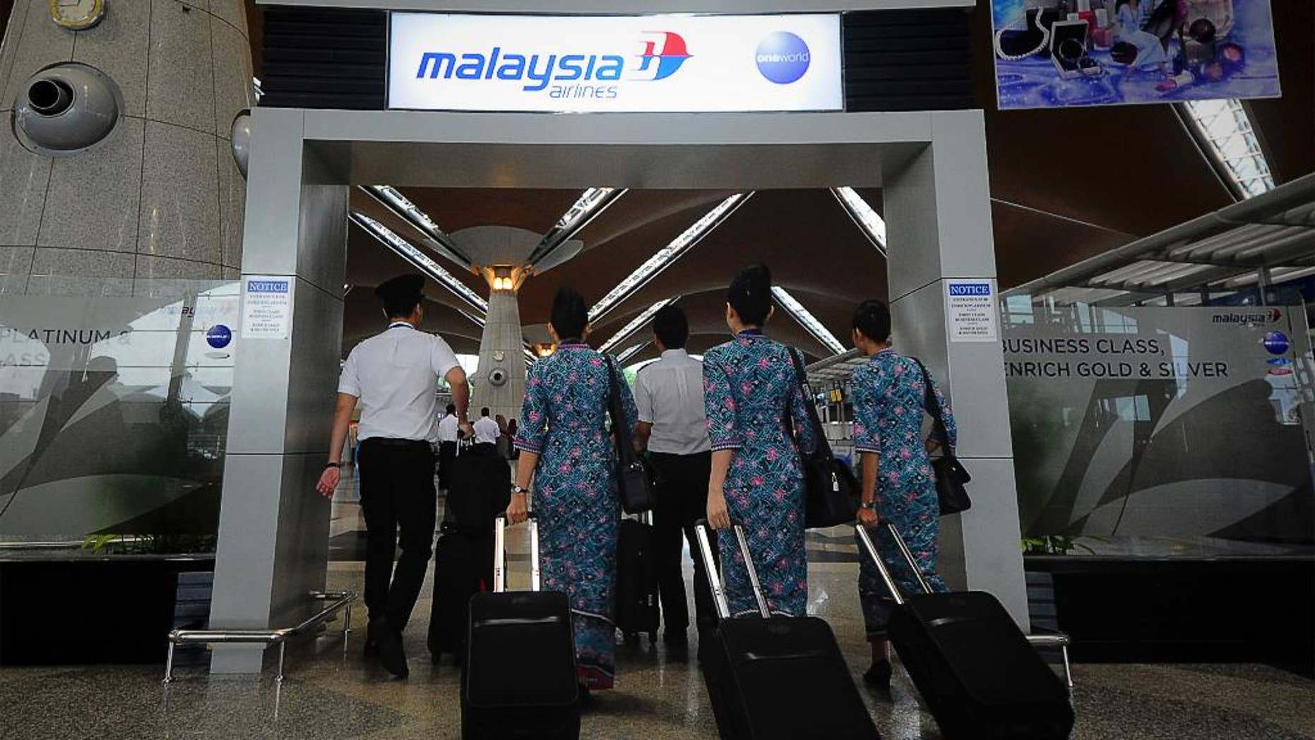"""FILE - In this April 10, 2014, file photo, a Malaysia Airlines crew walks into a check in area at Kuala Lumpur International Airport in Sepang, Malaysia. New Malaysia Airlines CEO, Christoph Mueller, 52, comes to the post fresh from a stint reviving Ireland's Aer Lingus. Mueller will be the first foreigner to head the Malaysian state-owned company. Analysts say he's an industry veteran """"battle hardened"""" from his work carrying out corporate restructurings at other state-owned airlines, including failed Belgian carrier Sabena.  (AP Photo/Joshua Paul, File)"""