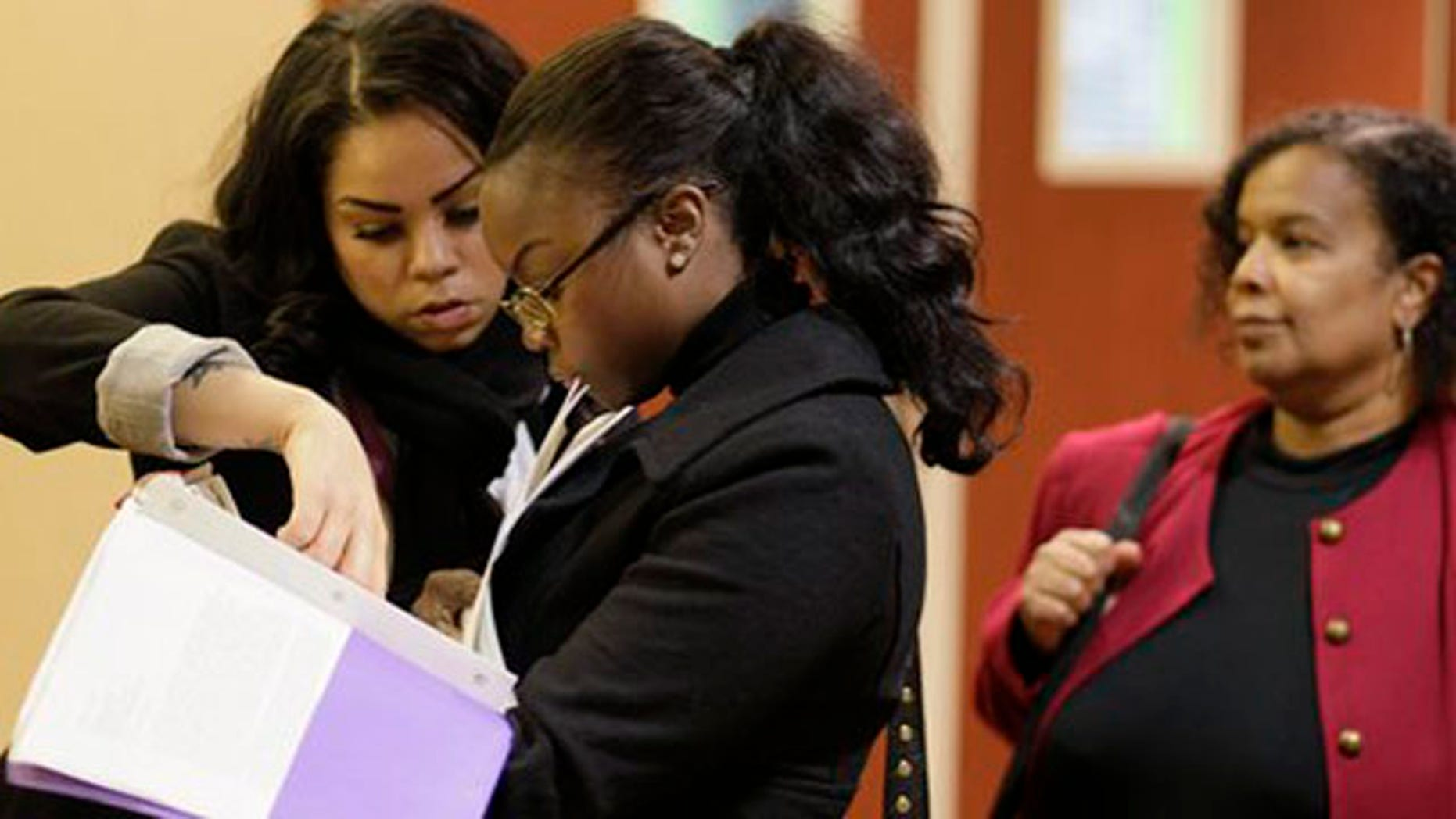Jan. 28, 2012: Job seekers Cameo Taylor, left, and Angelique McGuire, center, both of San Francisco, wait in line to register at a Career Fair event in San Francisco.