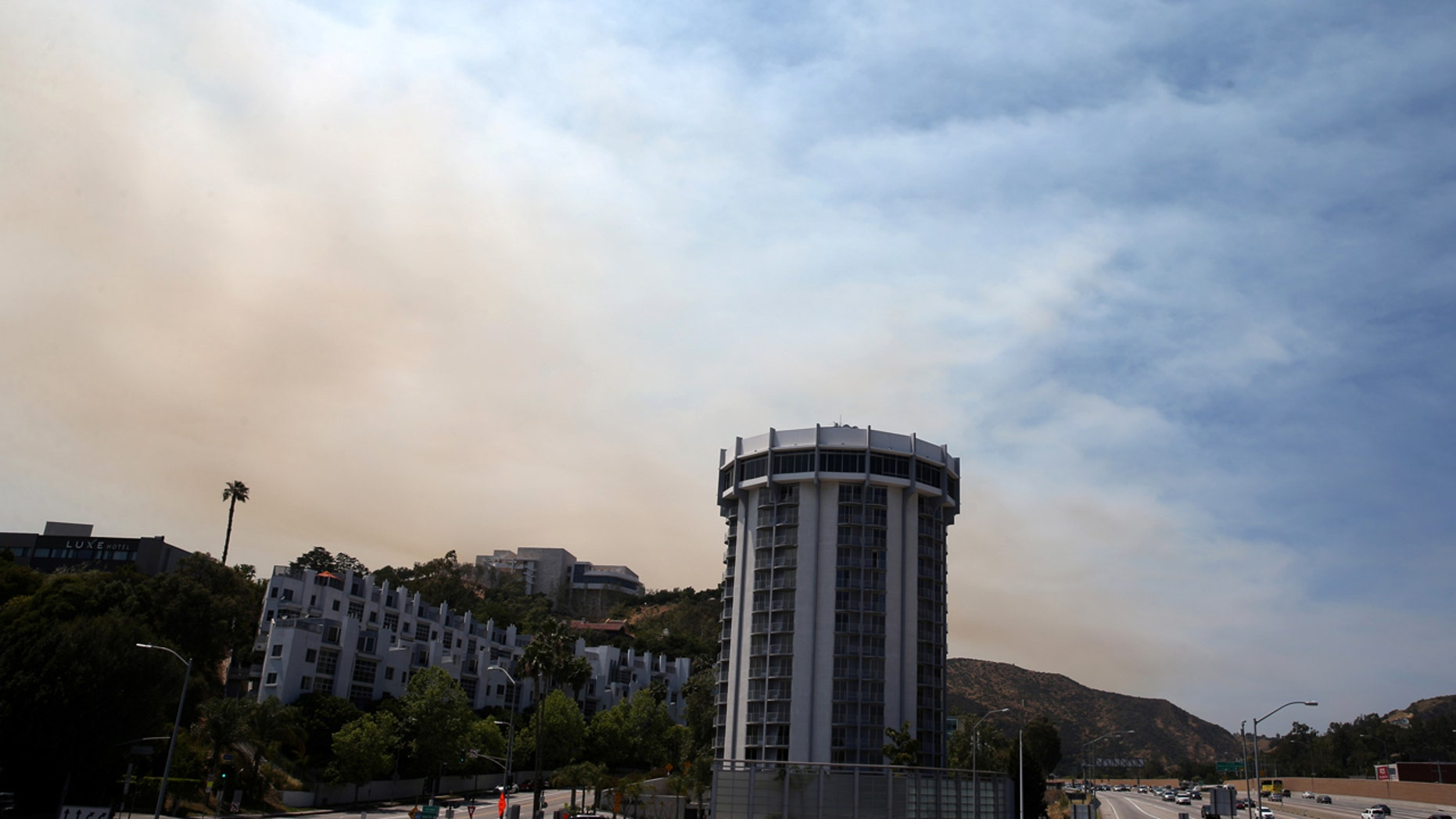 FILE: A wildfire burns behind Getty Center in Mandeville Canyon in Los Angeles