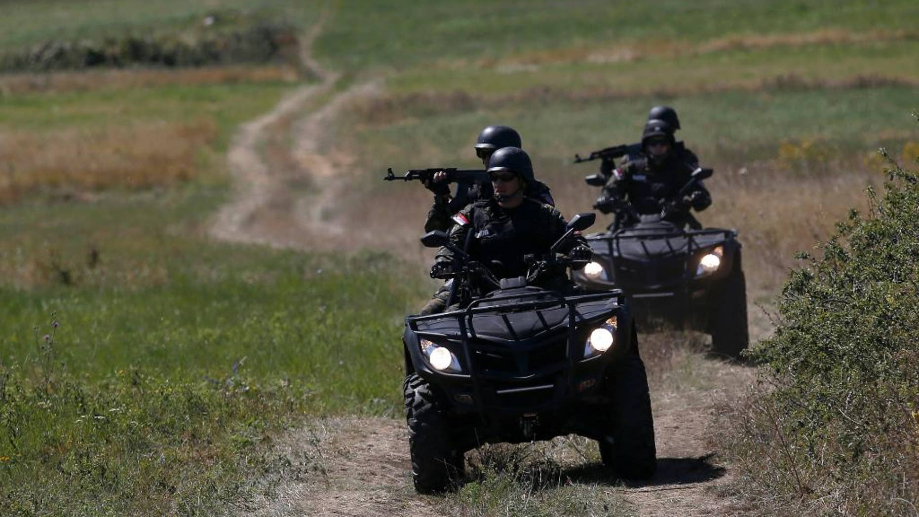 FILE - In this Aug. 15, 2016 file photo, Serbian officers patrol near the border between Serbia and Bulgaria, not far from the border crossing Vrska Cuka, about 250 kilometers (155 miles) southeast of Belgrade, Serbia. Serbia's president, speaking on Monday, Oct. 3, 2016, said that the Balkan country would seal its borders to stop migrants if the European Union countries further along the migration route fully block their boundaries against people fleeing war and poverty. (AP Photo/Darko Vojinovic, File)