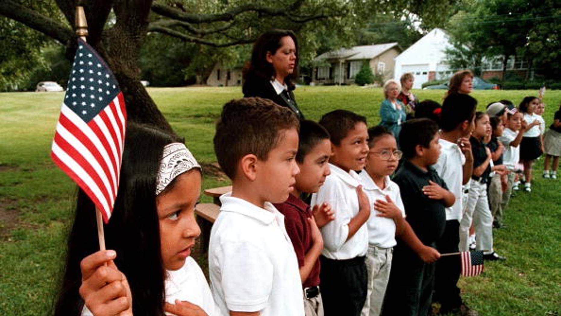 TYLER,TX - SEPTEMBER 11:  A class of Hispanic students recites the Pledge of Allegiance during a September 11 memorial service at Birdwell Elementary School September 11, 2003 in Tyler, Texas. Birdwell has a student body of 600 youngsters, with 60 percent of them being Hispanic. Among the other schools in the Tyler Independent School District, 30 percent of the 17,550 students are Hispanic, according to school district administrators.  (Photo by Mario Villafuerte/Getty Images)