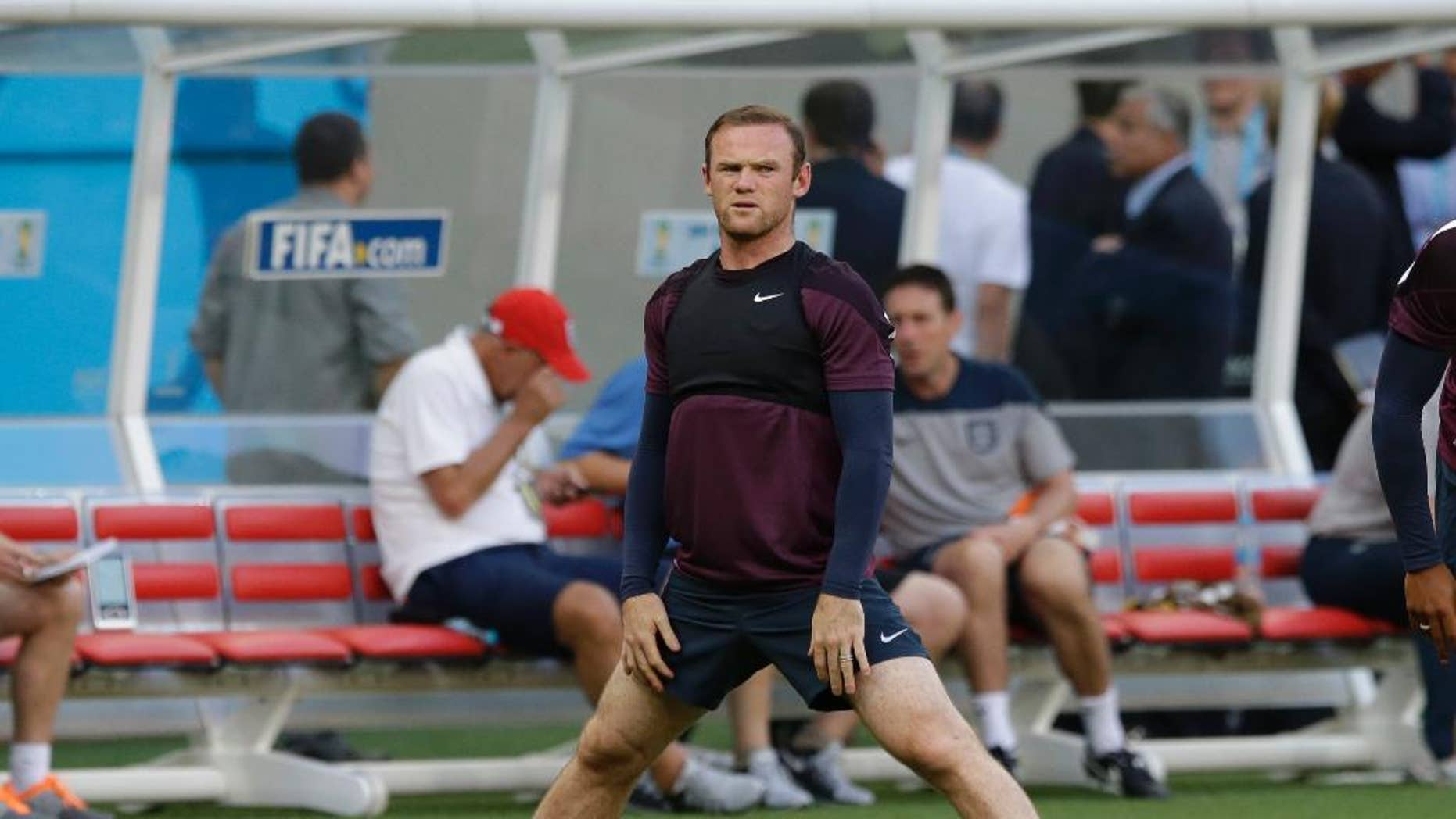 England's Wayne Rooney stretches as he takes part in a training session of the England national soccer team at the Arena da Amazonia in Manaus, Brazil, Friday, June 13, 2014.  England play Italy in group D of the 2014 soccer World Cup at the stadium on Saturday.  (AP Photo/Matt Dunham)