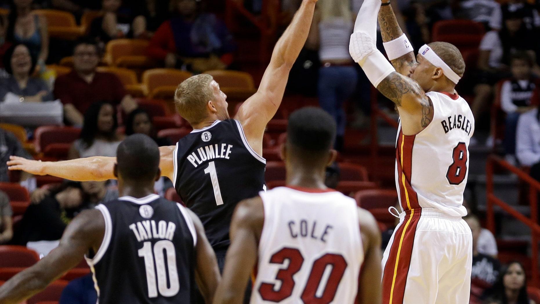 Miami Heat small forward Michael Beasley (8) prepares to take a shot as Brooklyn Nets power forward Mason Plumlee (1) defends in the fourth quarter of an NBA preseason basketball game, Friday, Oct. 25, 2013, in Miami. The Nets won 108-87. (AP Photo/Alan Diaz)