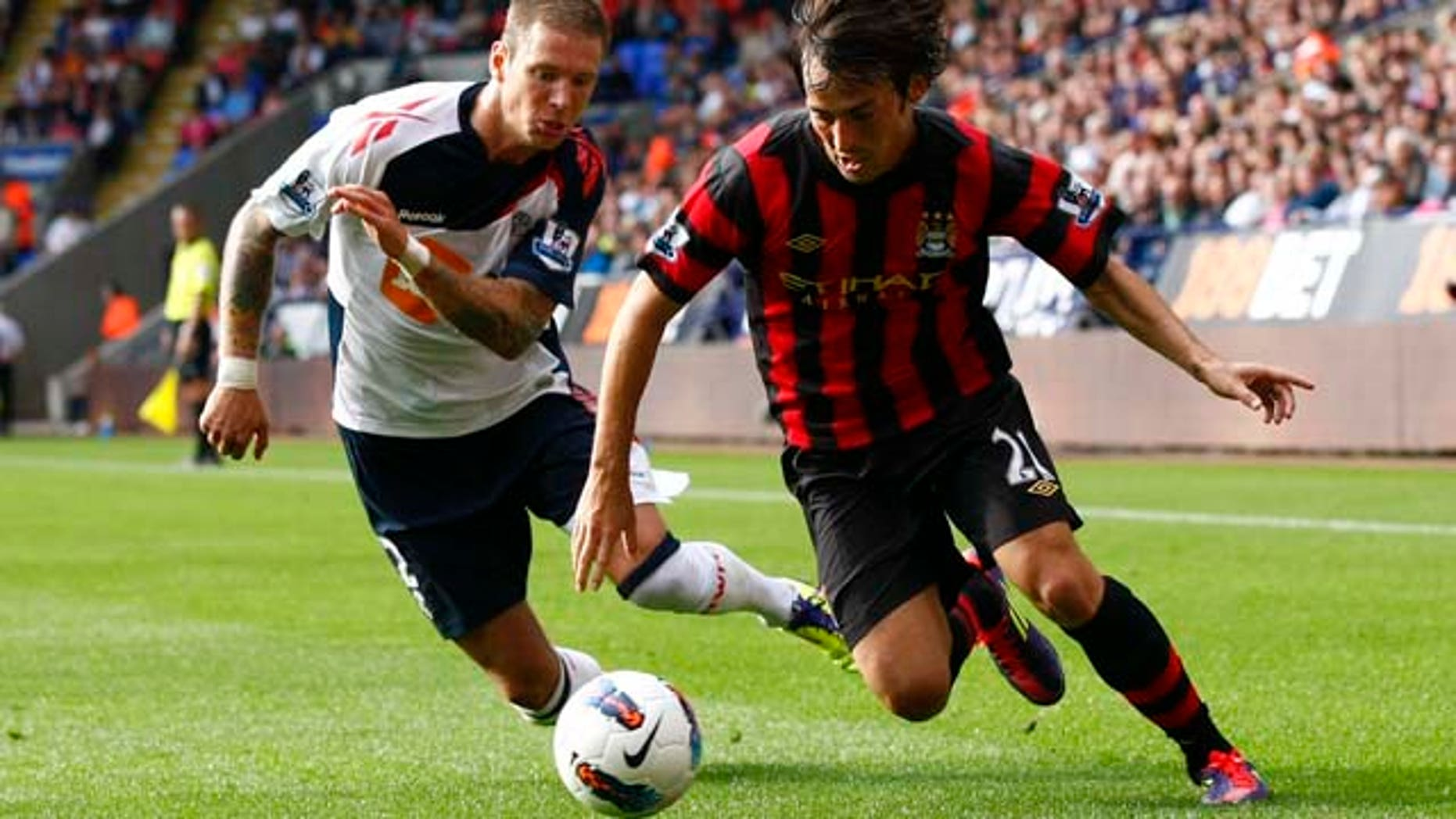 Manchester City's David Silva, right, vies for the ball against Bolton's Gretar Steinsson during their English Premier League soccer match at the Reebok Stadium, Bolton, England, Sunday Aug. 21, 2011. (AP Photo/Tim Hales)