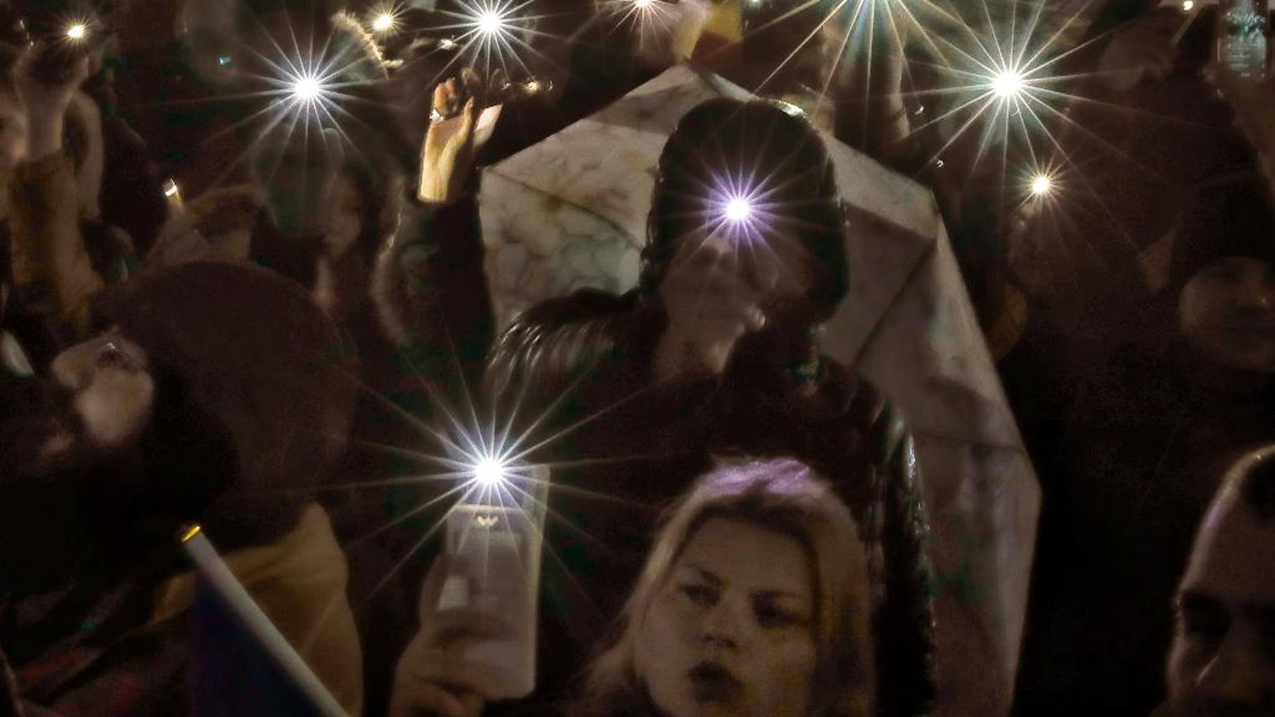 Protesters shine lights of their mobile phones while singing the national anthem outside the government headquarters in the rain in Bucharest, Romania, Sunday, Feb. 19, 2017. Braving the bad weather thousands gathered for the twentieth consecutive day to demand the government's resignation after it passed a decree, since withdrawn, that would have softened the corruption fight that has targeted top officials. (AP Photo/Vadim Ghirda)