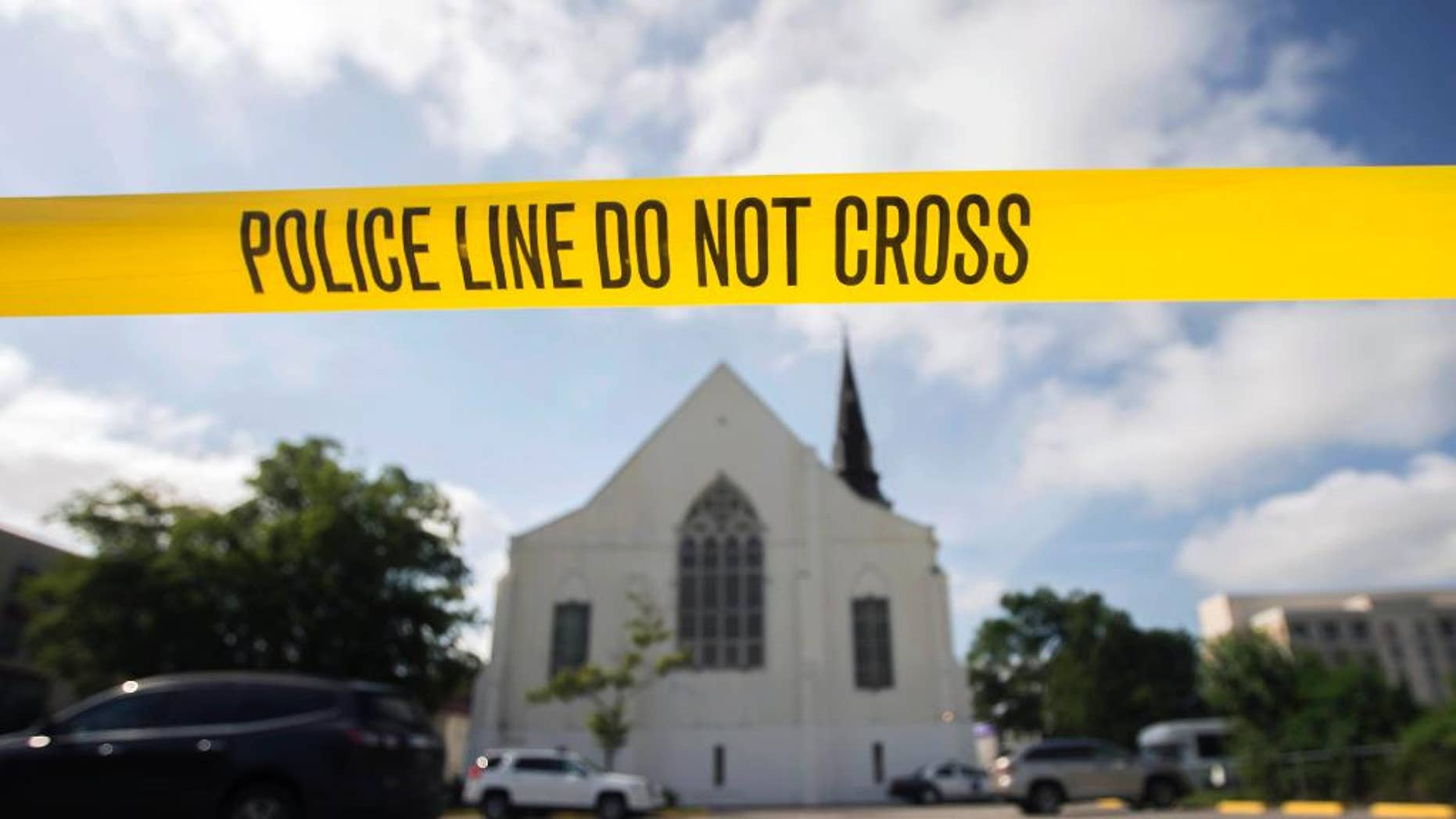 FILE - In this Friday, June 19, 2015 file photo, police tape surrounds the parking lot behind the AME Emanuel Church, a predominantly black church, as FBI forensic experts work at the crime scene where nine people where shot by white suspect Dylann Storm Roof, 21, on Wednesday in Charleston, S.C. The FBI collects extensive data on hate crimes each year, but nearly 2,800 local law enforcement agencies are not submitting the information, according to an investigation of 2009-2014 data by The Associated Press. Thousands more file reports with the FBI only sporadically. (AP Photo/Stephen B. Morton, File)