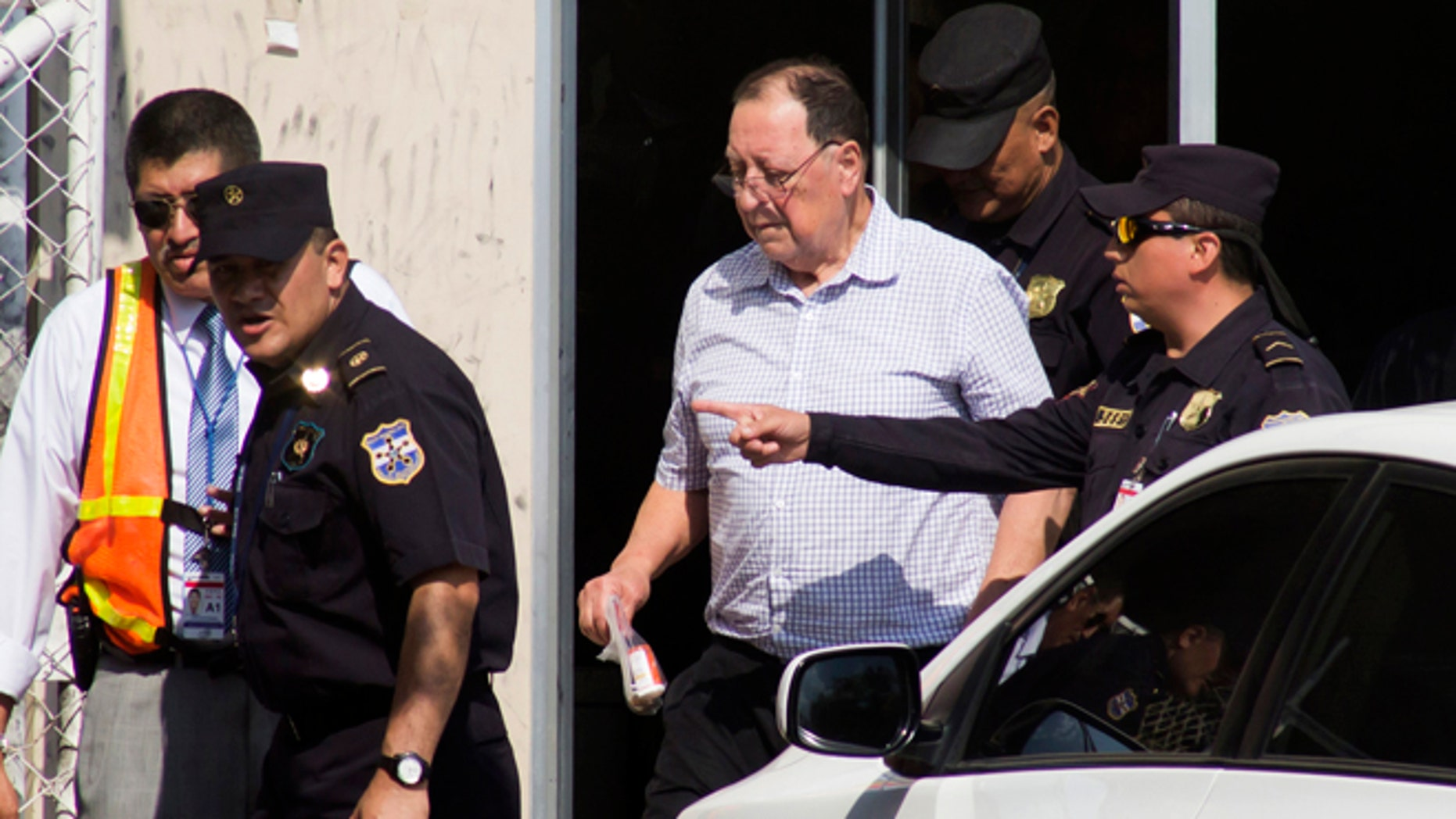 Police escort former General Eugenio Vides Casanova to a car outside the airport in San Salvador, El Salvador, Wednesday, April 8, 2015. The ex-general linked to human rights abuses during El Salvador's civil war in the 1980's was deported by the U.S. and flown to his home country, where officials said he faces no charges or restrictions on his movements. (AP Photo/Salvador Melendez)