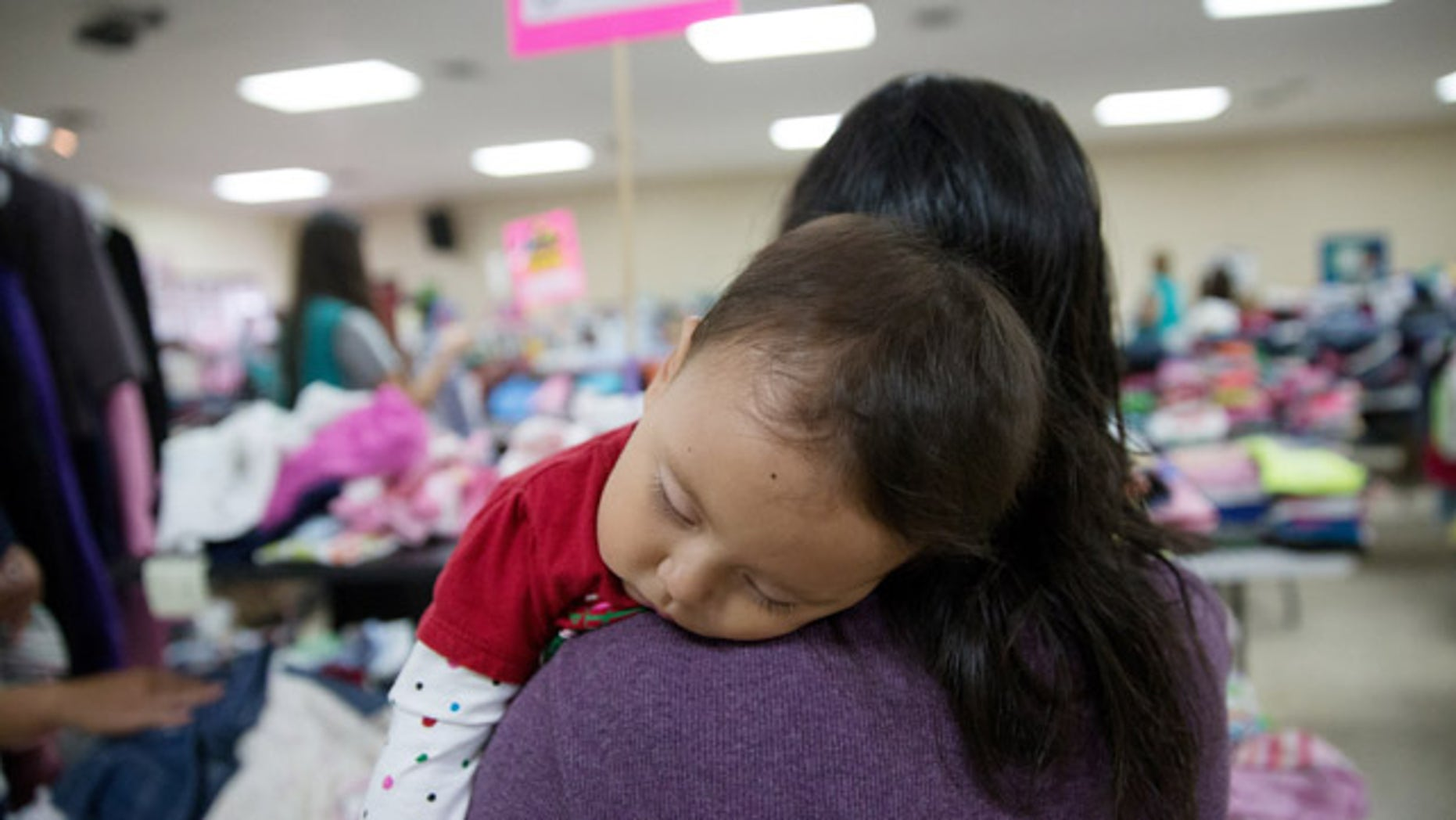 In this April 30, 2105 photo, Gladys Pina, 30, from Honduras holds her 8-month old baby girl at a respite center run by Catholic Charities in McAllen, Texas. She was among nearly two-dozen immigrant mothers who arrived at the center after being released by Border Patrol. Rather than getting locked up in a family detention facility, some families are released by Border Patrol with notices to appear in immigration court. (AP Photo/Seth Robbins)