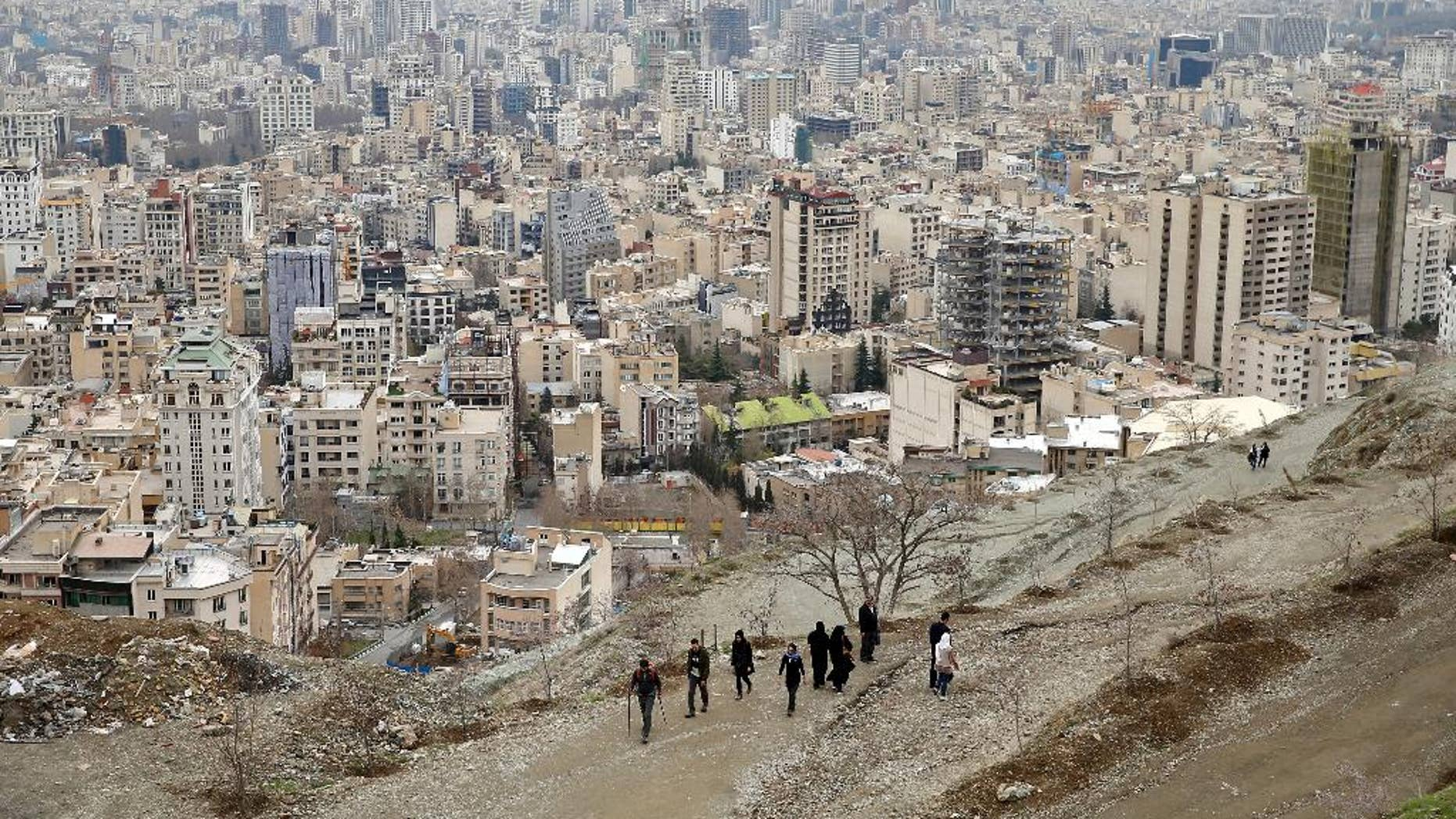 This Sunday, April, 2, 2017, shows Iranian hikers coming down from the mountain at the Tochal mountainous area in northern Tehran, Iran. Two days before what has been described as Tehran's first international marathon, a top Iranian sports official cannot confirm whether Americans will participate and says women will be forced to run separately from men. (AP Photo/Ebrahim Noroozi)