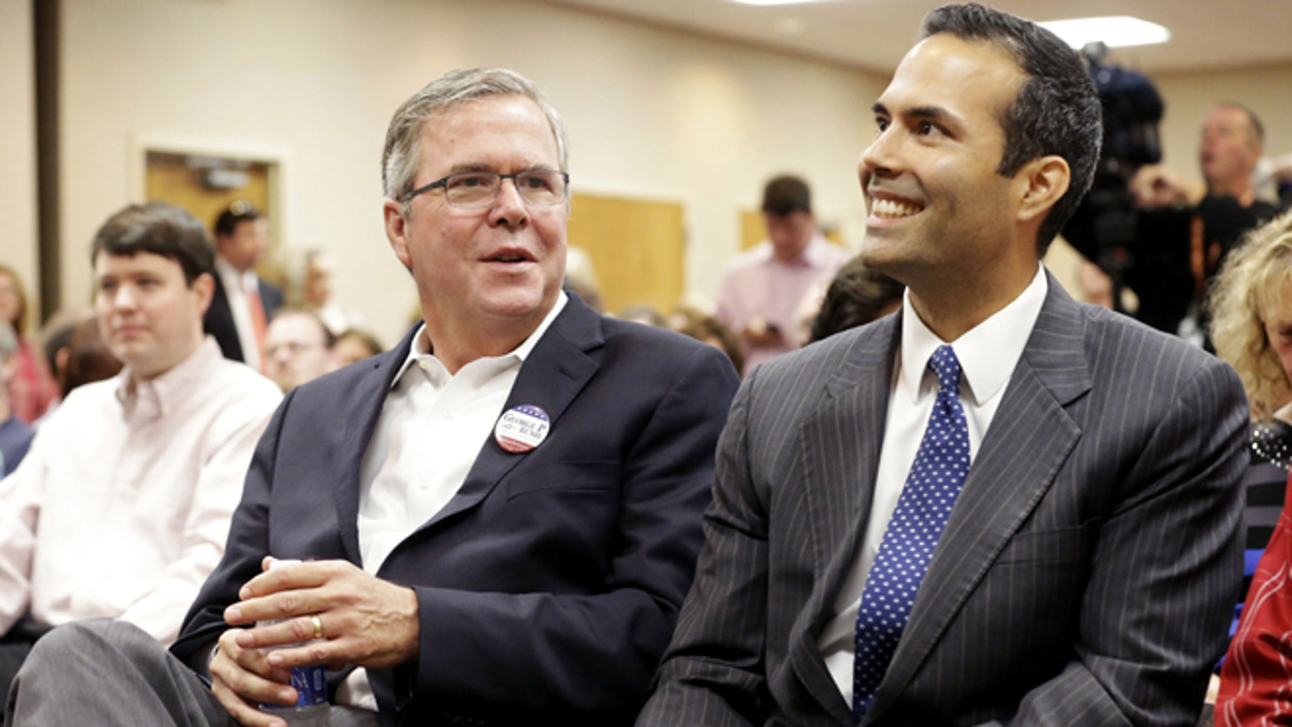 Former Florida Gov. Jeb Bush, left, sits with his son George P. Bush before speaking to supporters at Hardin-Simmons University, Tuesday, Oct. 14, 2014, in Abilene, Texas. Jeb Bush heads into West Texas to campaign for his son who is on the ballot this November as a candidate for state land commissioner. (AP Photo/LM Otero)