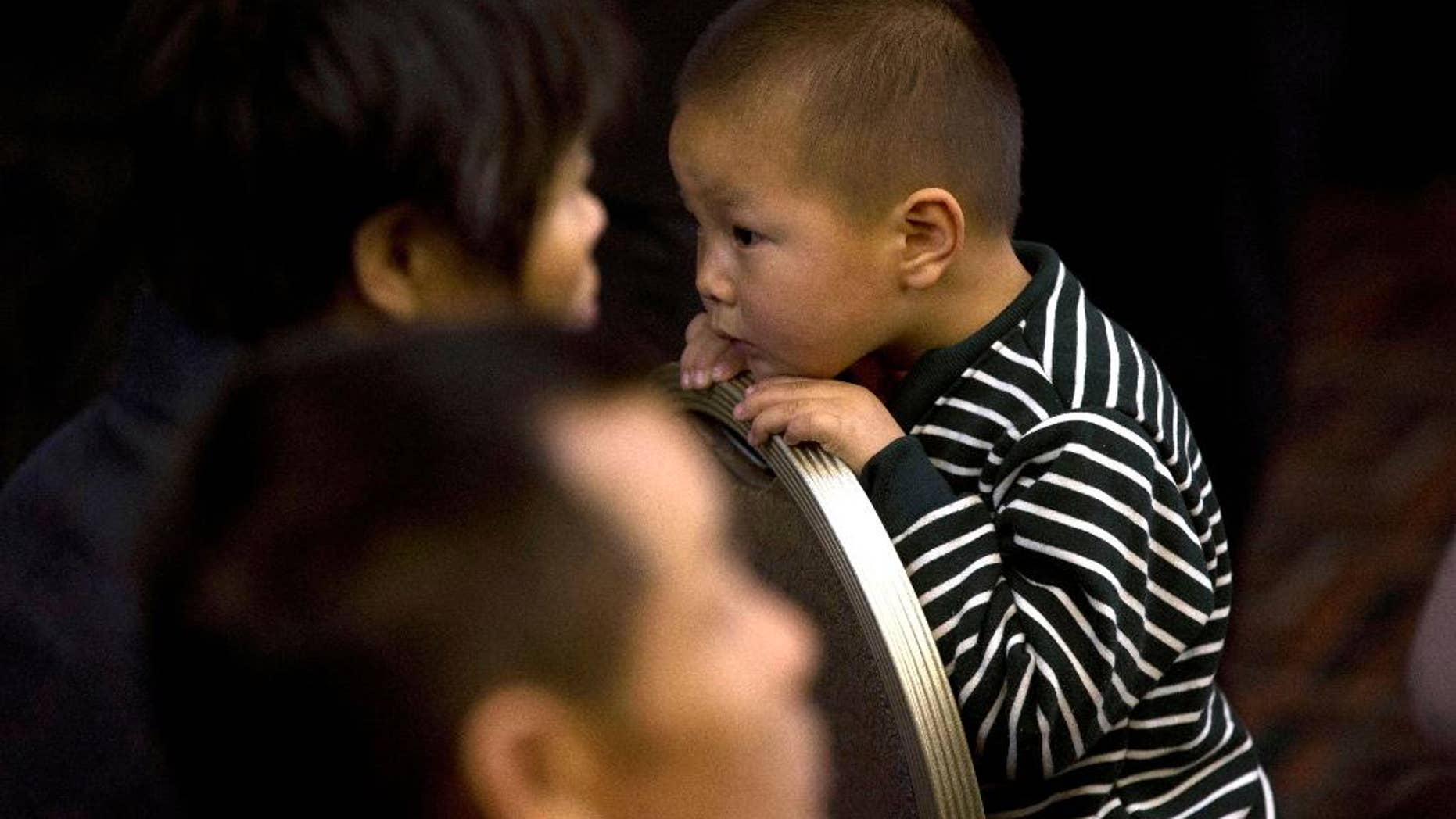 A child waits at a room reserved for relatives of Chinese passengers aboard the missing Malaysia Airlines flight MH370 in Beijing, China, Monday, March 24, 2014. Rain was expected to hamper the hunt Monday for debris suspected of being from the missing Malaysia Airlines jet, as the United States prepared to move a specialized device that can locate black boxes into the south Indian Ocean region.  (AP Photo/Ng Han Guan)
