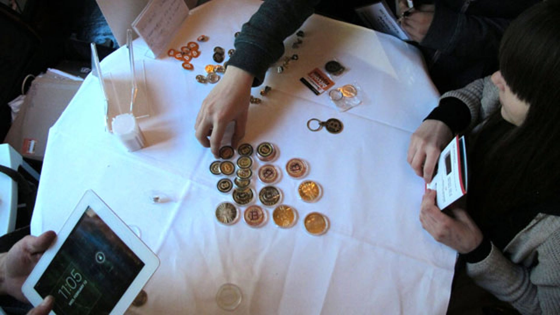FILE - In this Feb. 12, 2014 file photo, attendees of the Inside Bitcoins conference in Berlin examine Bitcoin buttons. (AP Photo)