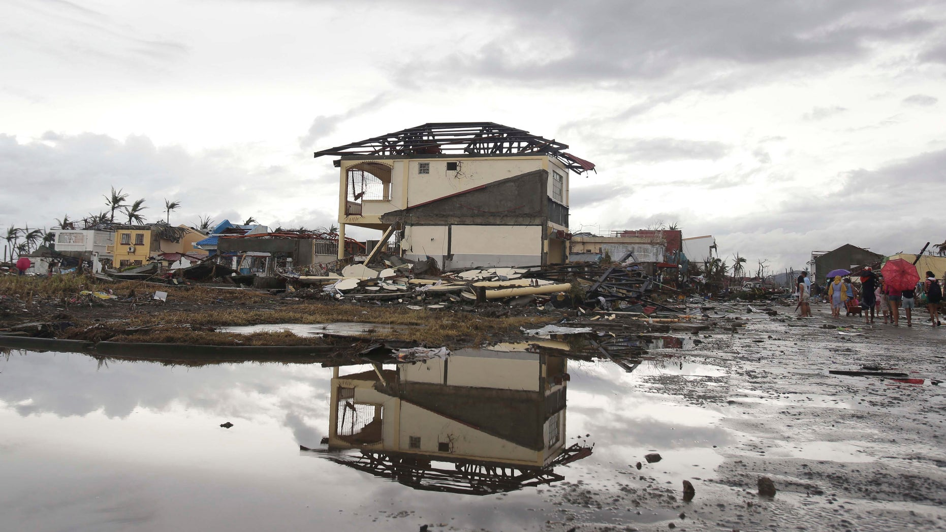 Nov. 12, 2013: Survivors walk past damaged houses at typhoon ravaged Tacloban city, Leyte province, central Philippines. The Philippines emerged as a rising economic star in Asia but the trail of death and destruction left by Typhoon Haiyan has highlighted a key weakness: fragile infrastructure resulting from decades of neglect and corruption.