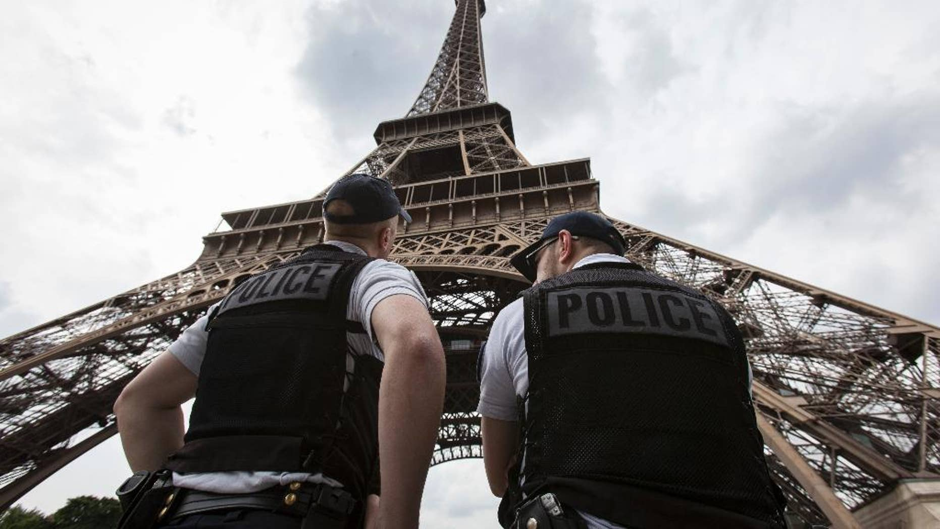 FILE- In this Friday, June 10, 2016 file photo, French riot police officers patrol under the Eiffel Tower, near the entrance of the soccer fan zone, prior to the Euro 2016 Group A soccer match between France and Romania, in Paris. Paris authorities say Thursday, Feb. 9, 2017, they are proposing to replace the metal security fencing around the Eiffel Tower with a more aesthetic glass wall. (AP Photo/Kamil Zihnioglu, File)