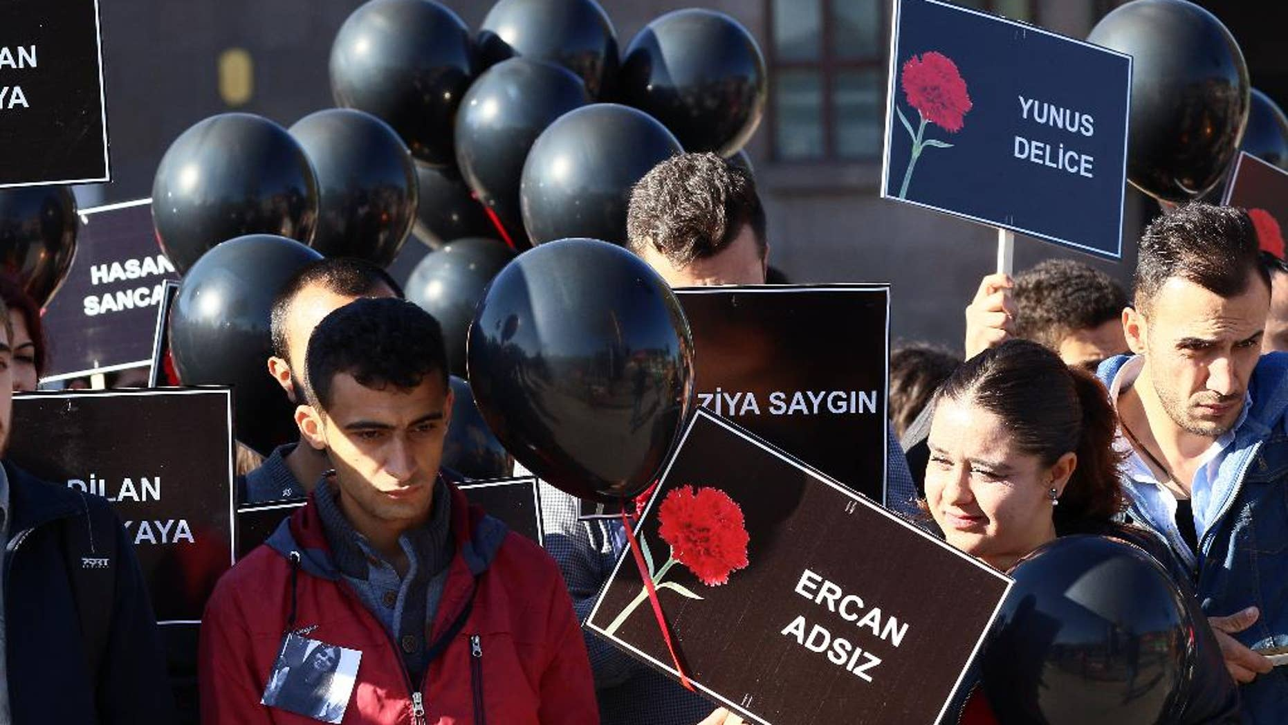 Members of youth organzations hold names of victims and black balloons as they gather at the site of twin explosions that killed 102 people and injured hundreds others more than two weeks ago outside the main train station in Ankara, Turkey, Monday, Oct. 26, 2015. (AP Photo)
