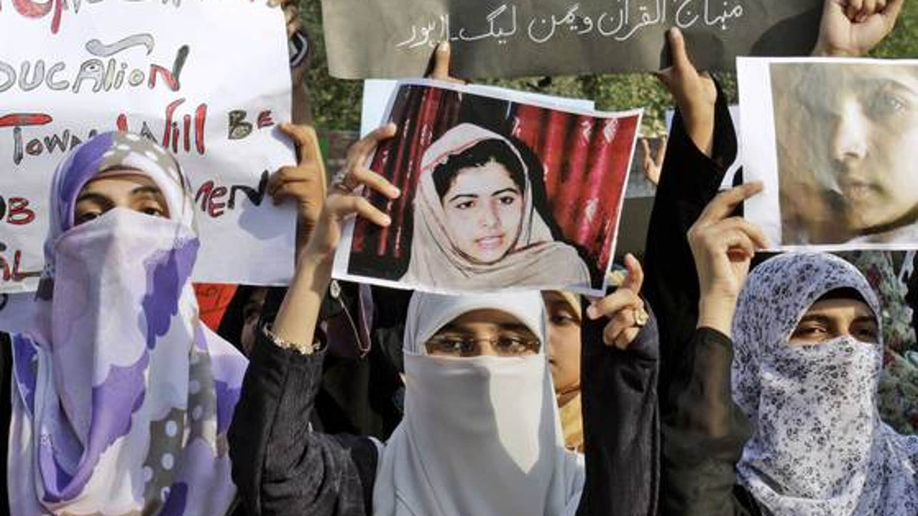 October 10, 2012: Pakistani members of Minhaj-ul-Quran Women League hold up pictures of 14-year-old schoolgirl Malala Yousufzai in Lahore, Pakistan.