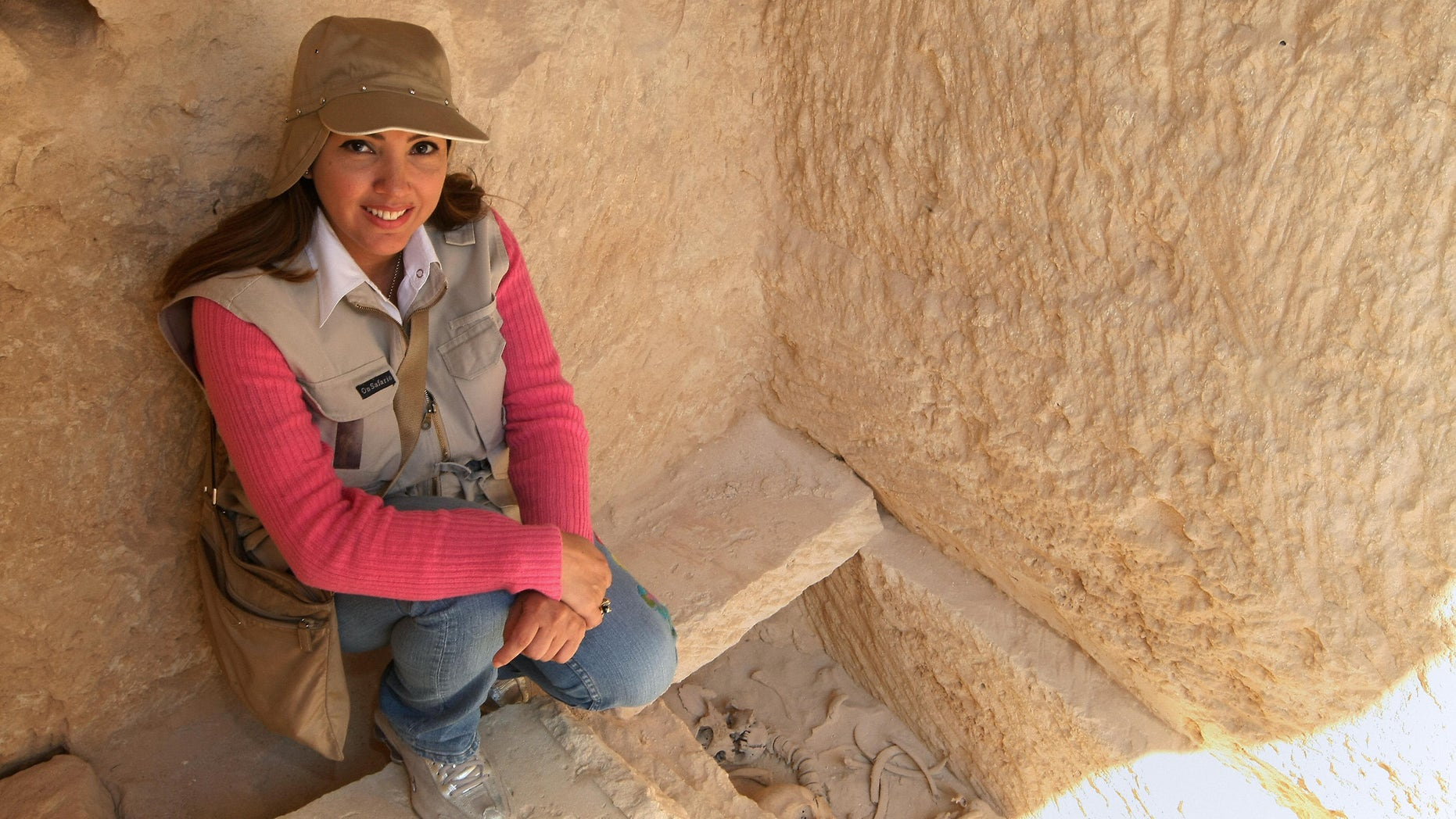 Kathleen Martinez, an Egyptologist from the Dominican Republic, sits near a grave found at the temple of Tasposiris Magna near Borg al-Arab, 50 kms (30 miles) west of Alexandria, on April 19, 2009. Archaeologists searching for the tomb of Marc Anthony and Cleopatra may be closer to locating the burial site of the legendary lovers, Egypt's antiquities council said. A team led by antiquities chief Zahi Hawass and Martinez believes the tomb may be located in three possible sites near the temple and will excavate the three locations next week. AFP PHOTO/CRIS BOURONCLE (Photo credit should read CRIS BOURONCLE/AFP/Getty Images)