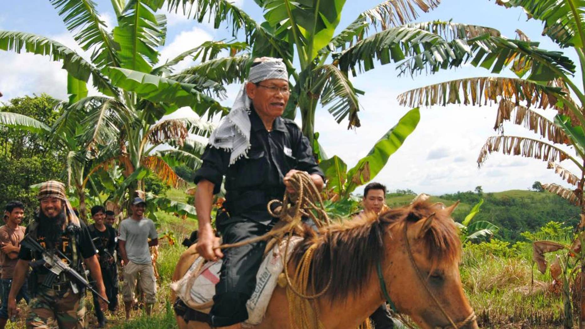 FILE - In this file photo taken Tuesday, Aug. 16, 2011, Ameril Umbra Kato, the commander of the Bangsamoro Islamic Freedom Movement, rides a horse inside his rebel stronghold in Maguindanao province in southern Philippines. The commander whose rebels have pledged support to the Islamic State group died Tuesday following a long ailment, the Philippine military and insurgents said Wednesday, April 15, 2015. (AP Photo/Nickee Butlangan, File)