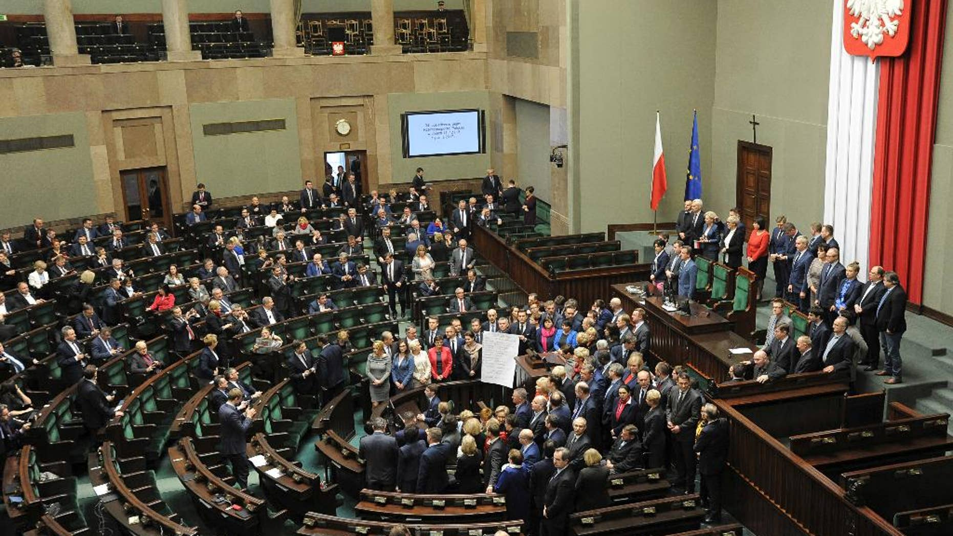 A general view of the parliament session hall as opposition lawmakers gather around the podium with a list of ten freedoms that they say are violated by the ruling party, as they end their protest, in Warsaw, Poland, Thursday, Jan. 12, 2017. Opposition parties blocked the session hall since Dec. 16 to protest a budget that according to them was passed illegally. (AP Photo/Alik Keplicz)