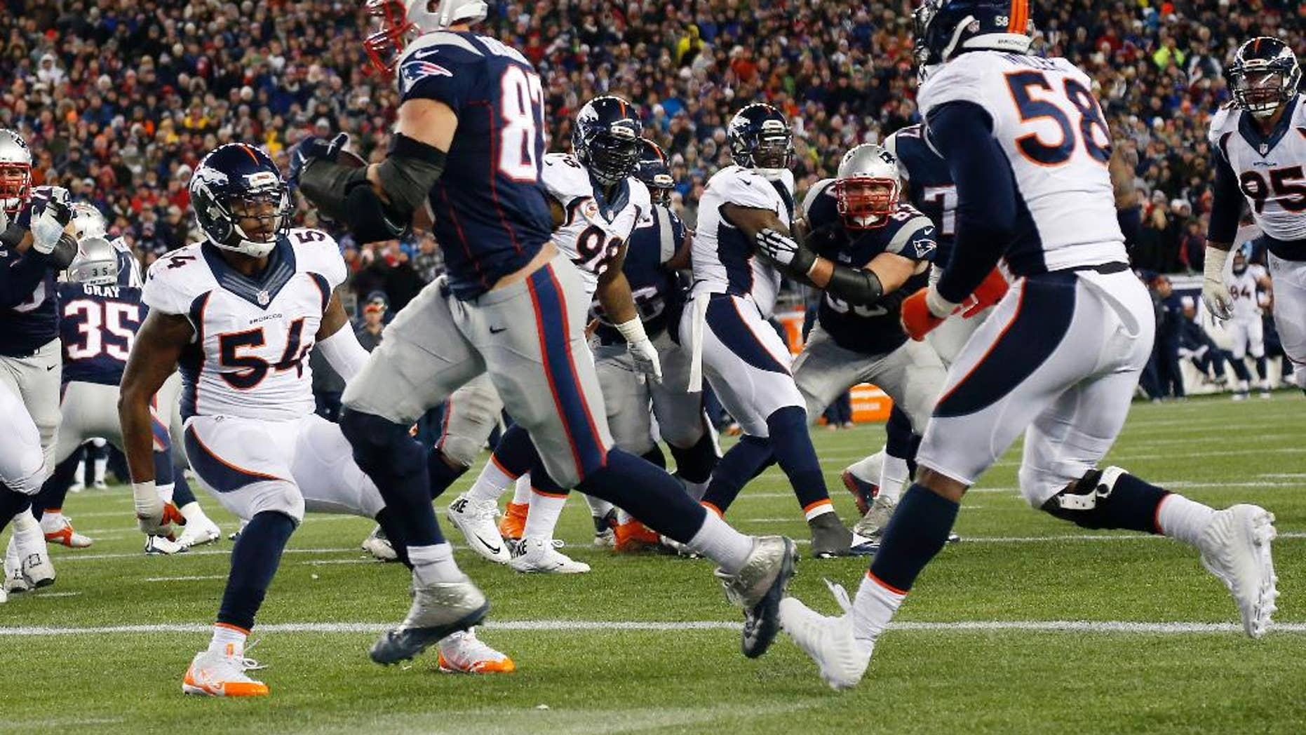 New England Patriots tight end Rob Gronkowski, center, catches a touchdown pass from quarterback Tom Brady between Denver Broncos outside linebackers Brandon Marshall (54) and Von Miller (58) in the second half of an NFL football game on Sunday, Nov. 2, 2014, in Foxborough, Mass. (AP Photo/Elise Amendola)