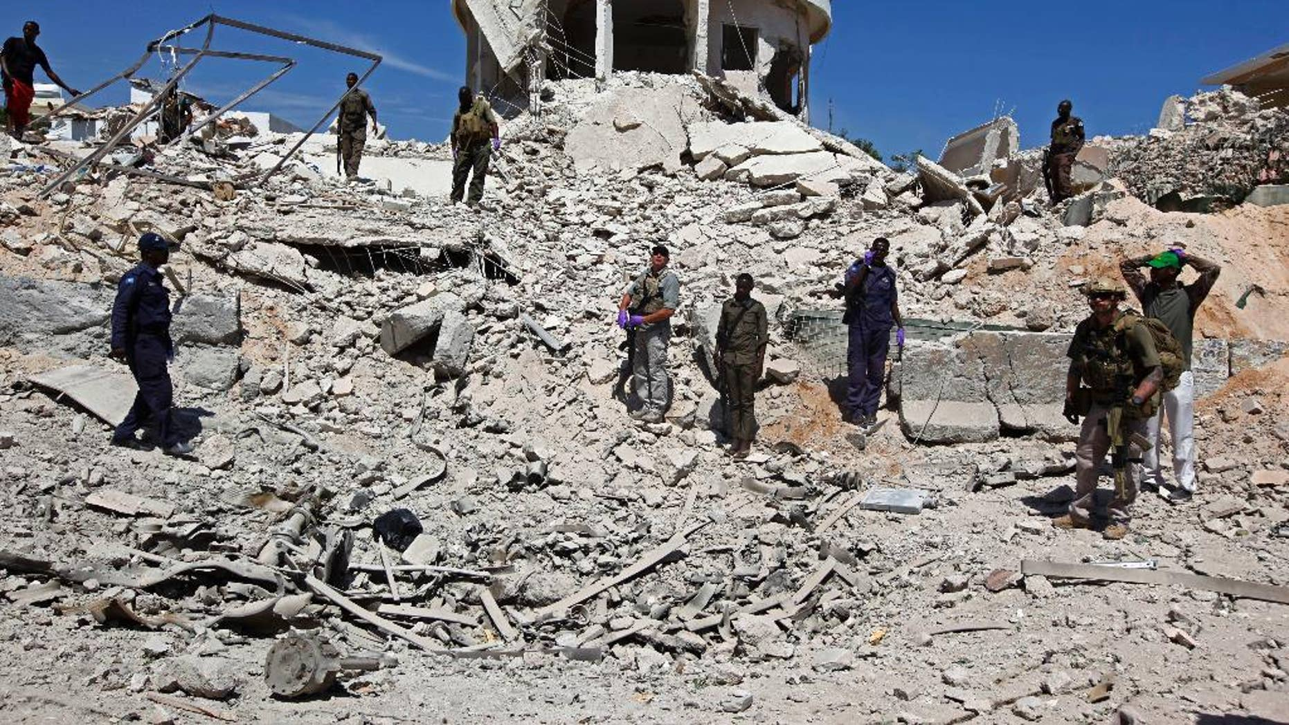 Soldiers stand in the rubble of a destroyed building near the scene of a suicide car bomb attack in Mogadishu, Somalia, Monday, Jan, 2, 2017. An attacker detonated an explosives-laden vehicle at a security checkpoint near Mogadishu's international airport, killing several people, according to a police officer. The assaults have threatened this Horn of Africa nation's attempts to rebuild from decades of chaos. The country's presidential election, a key step toward recovery, already has been delayed multiple times because of security and other concerns. (AP Photo/Farah Abdi Warsameh)