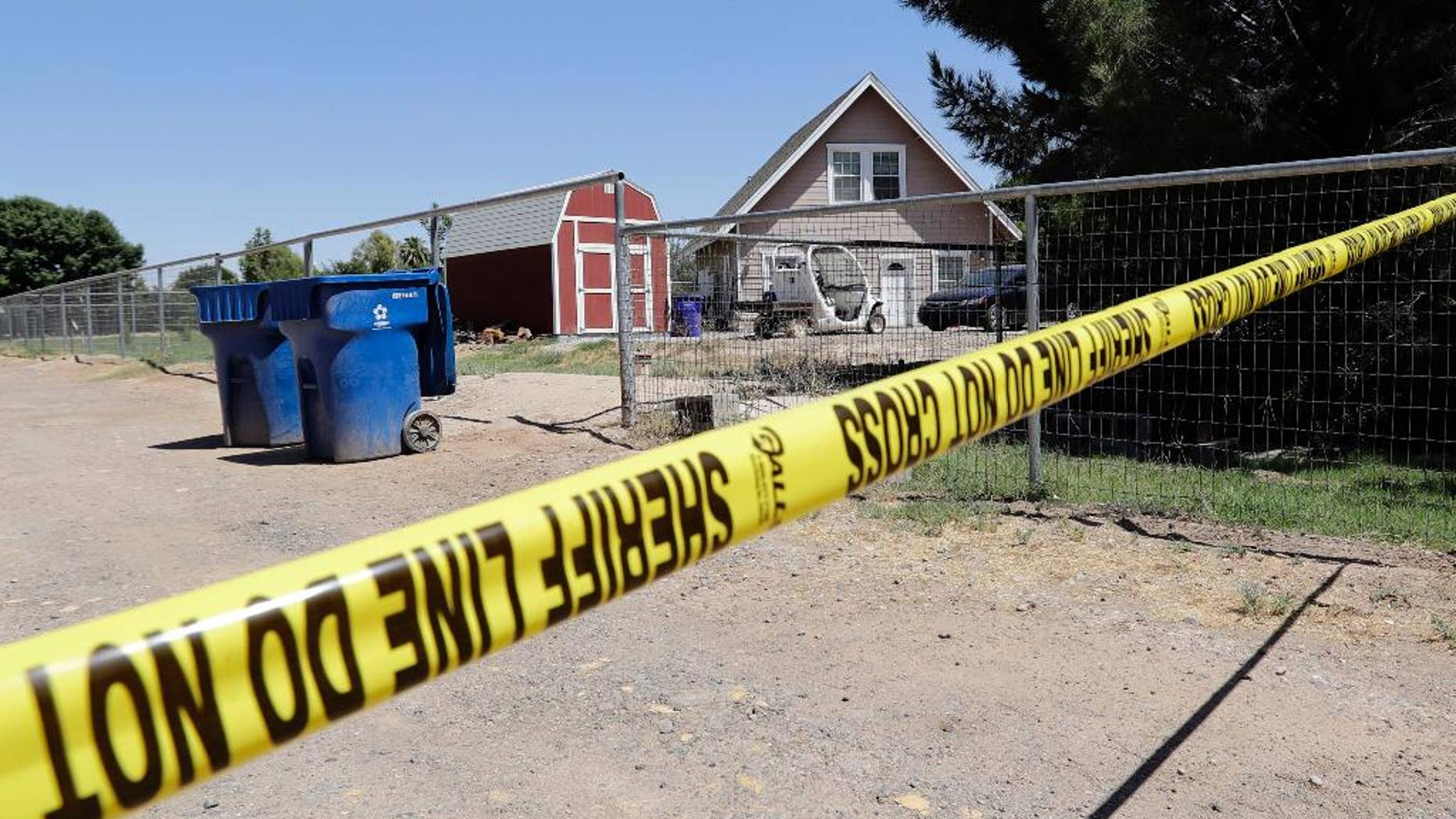 Crime scene tape blocks the entrance to a home where multiple bodies were found, Tuesday, July 26, 2016, in Gilbert, Ariz. Sheriff's officials say multiple dead bodies have been found inside a home in an unincorporated area of Gilbert, east of Phoenix. There's no immediate word Tuesday on how many bodies or their ages or genders. (AP Photo/Matt York)