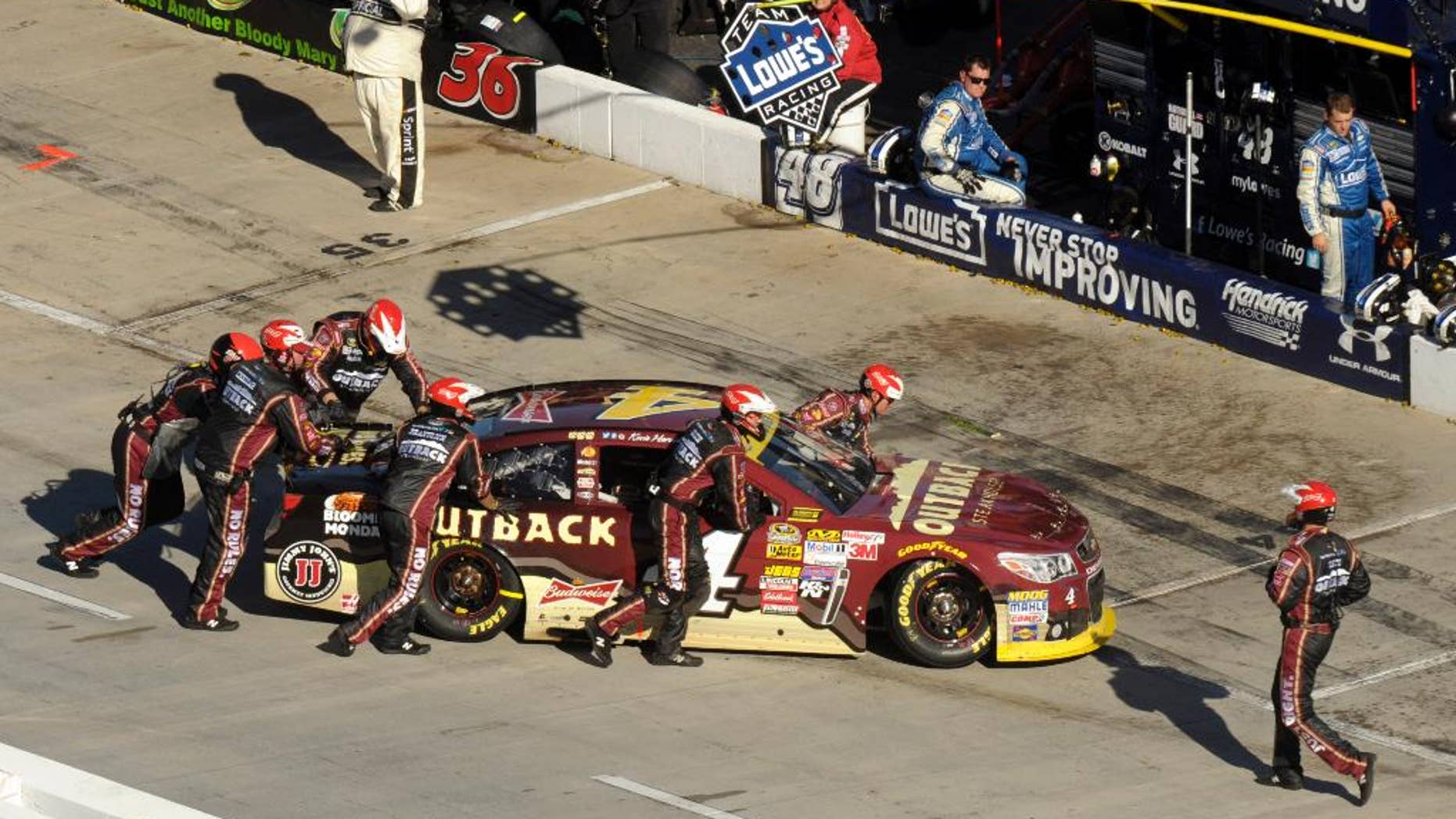 The pit crew for Kevin Harvick (4) pushes his car into the garage during the NASCAR Sprint Cup Series auto race at Martinsville Speedway in Martinsville, Va., Sunday, Oct. 26, 2014. (AP Photo/Don Petersen)
