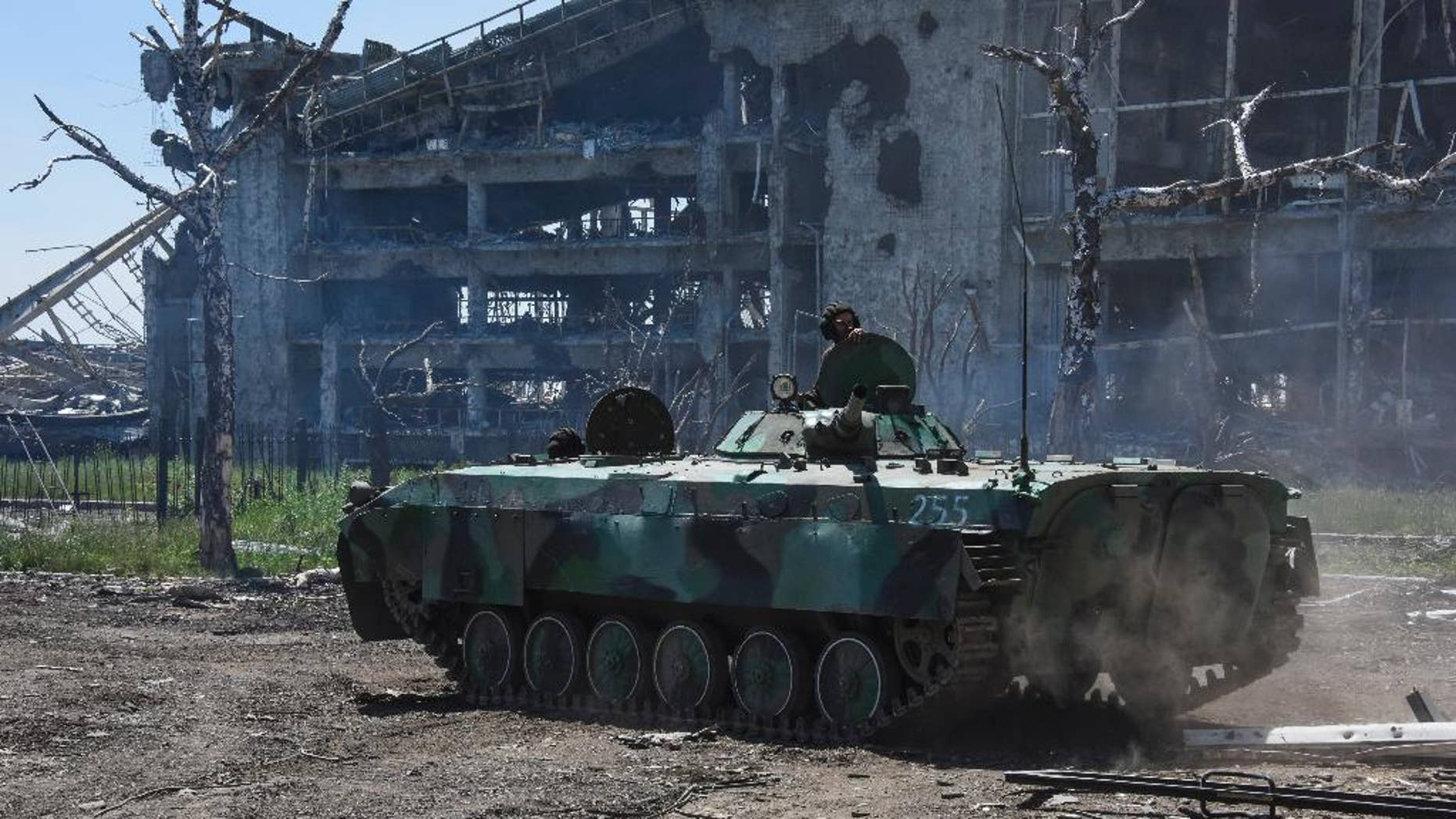 A Russia-backed armoured personnel carrier makes its way near positions at the destroyed building of Donetsk Airport just outside Donetsk, eastern Ukraine, Tuesday, June 9, 2015. Heavy fighting continue at the frontline at the airport of Donetsk. (AP Photo/Mstyslav Chernov)