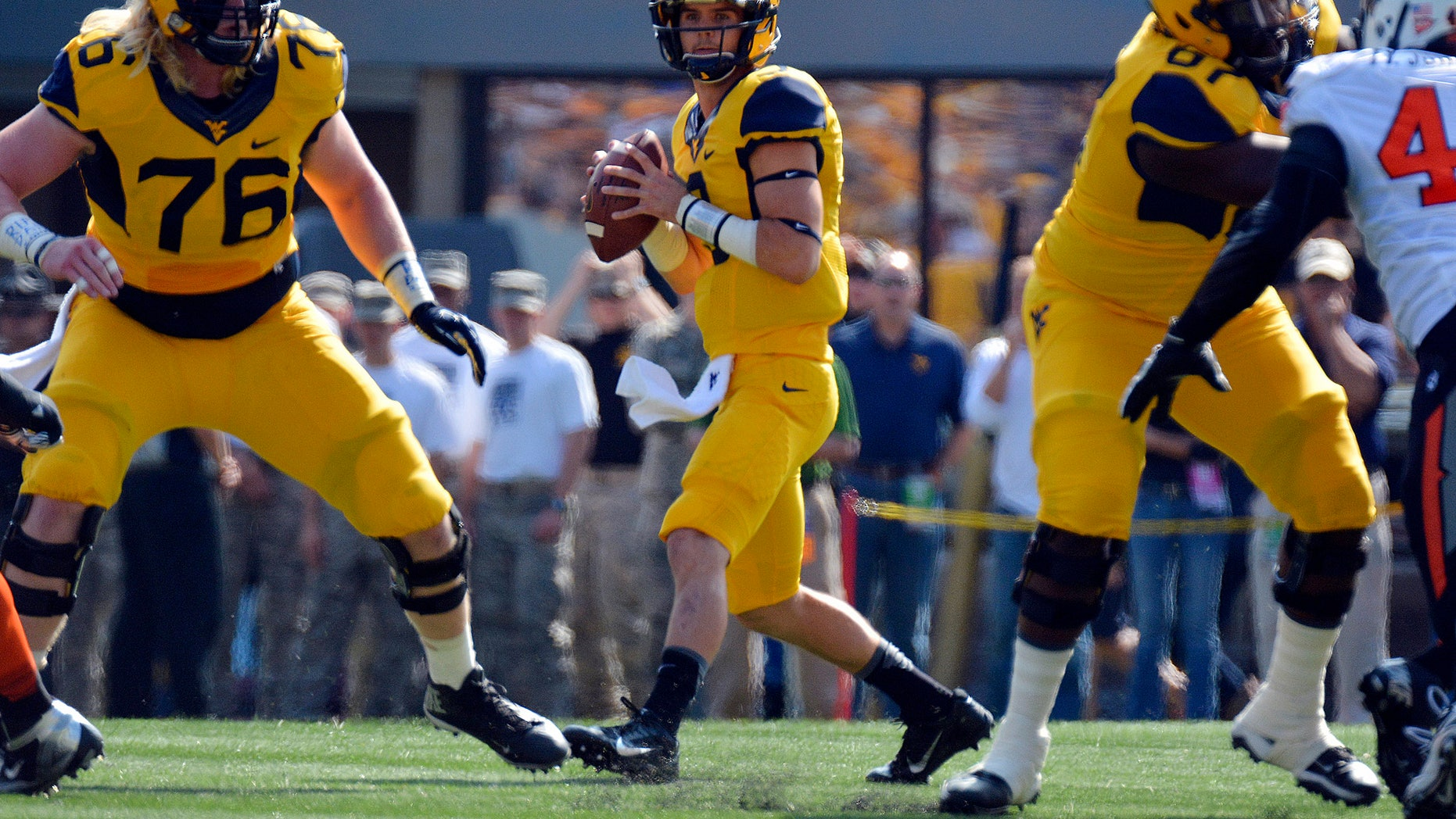 West Virginia quarterback Clint Trickett (9) looks for an open receiver during the first quarter of an NCAA college football game against Oklahoma State in Morgantown, W.Va., on Saturday, Sept. 28, 2013. (AP Photo/Tyler Evert)