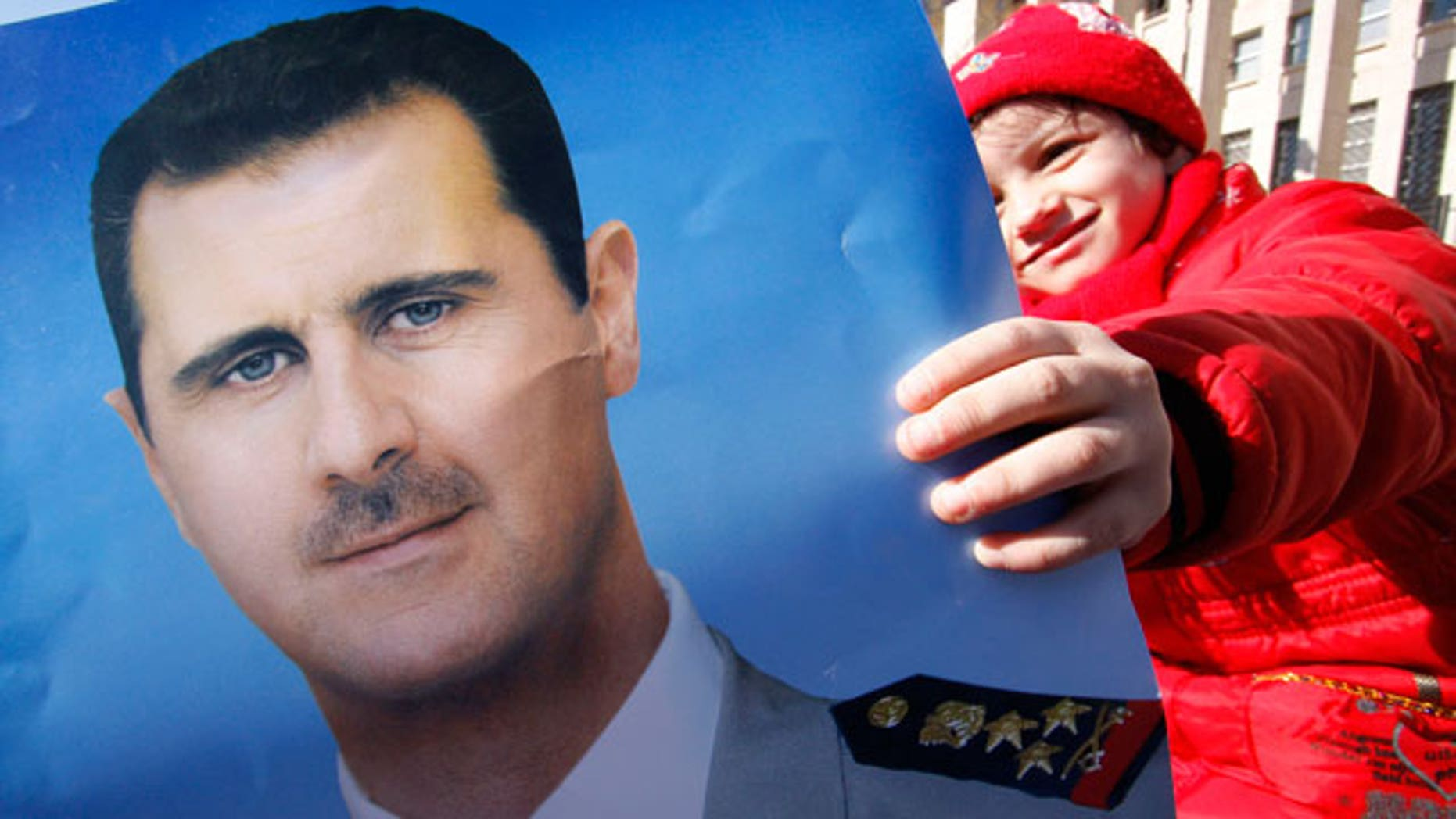 Jan. 20, 2012: A pro-Syrian regime protester holds a portrait of Syrian President Bashar Assad during a demonstration to show support for their president, in Damascus, Syria.