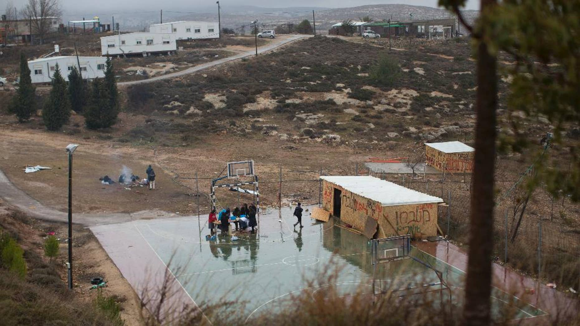 File - In this Sunday, Dec. 18, 2016 file photo, Jewish settlers cook food in a basketball field in Amona, an unauthorized Israeli outpost in the West Bank, east of the Palestinian town of Ramallah. A group of Palestinian landowners is set to reclaim the property they watched stripped from them two decades ago, hoping to finally put to rest a bitter, years-long battle that thrust them into a protracted legal saga and a political crisis that threatened to tear apart Israel's governing coalition. (AP Photo/Oded Balilty, File)